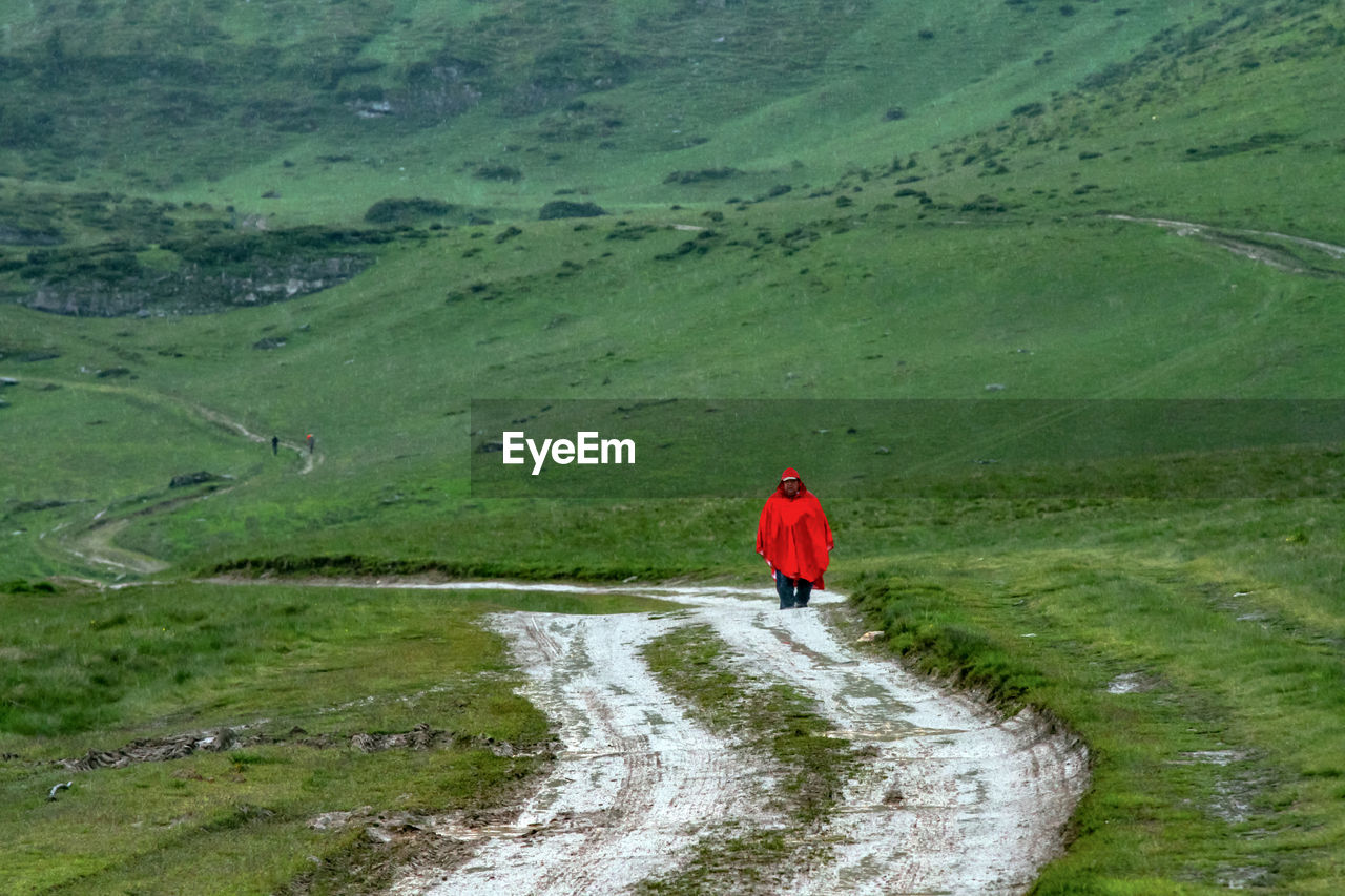 Man walking on dirt road against green mountain
