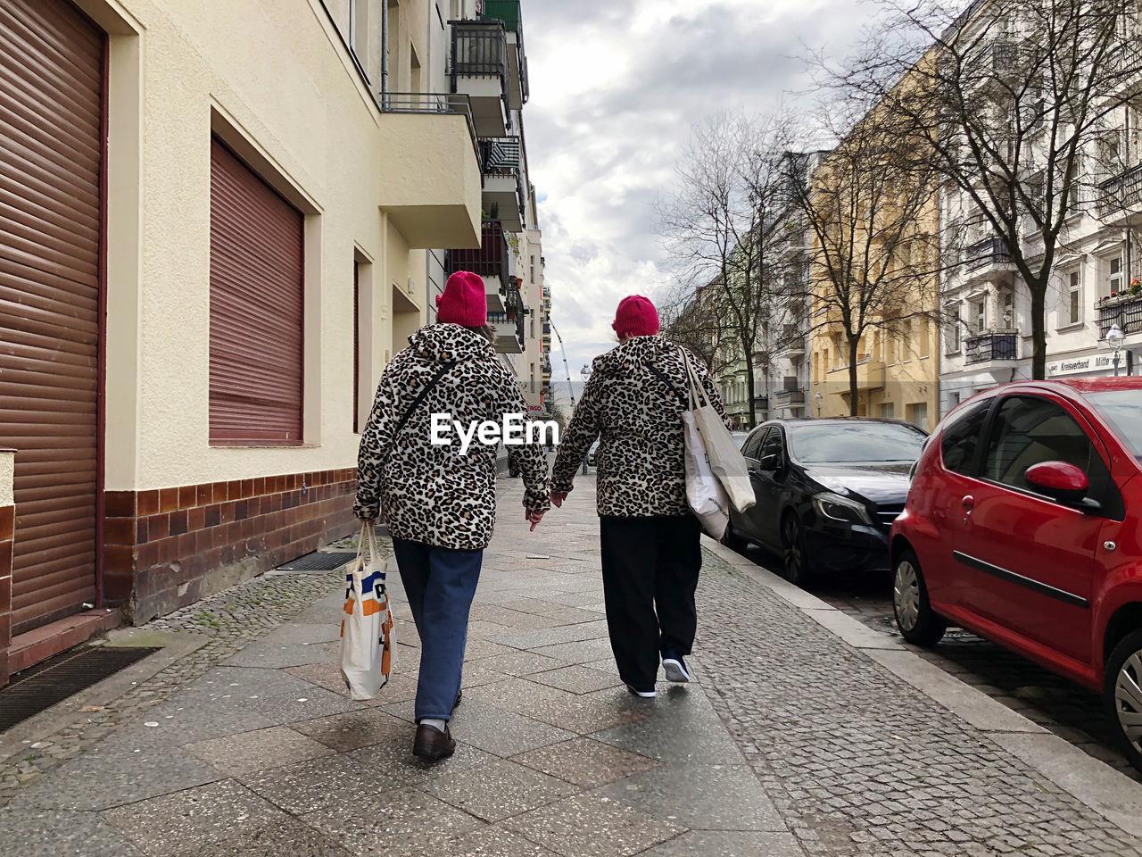 REAR VIEW OF WOMEN WALKING ON FOOTPATH AMIDST BUILDINGS IN CITY