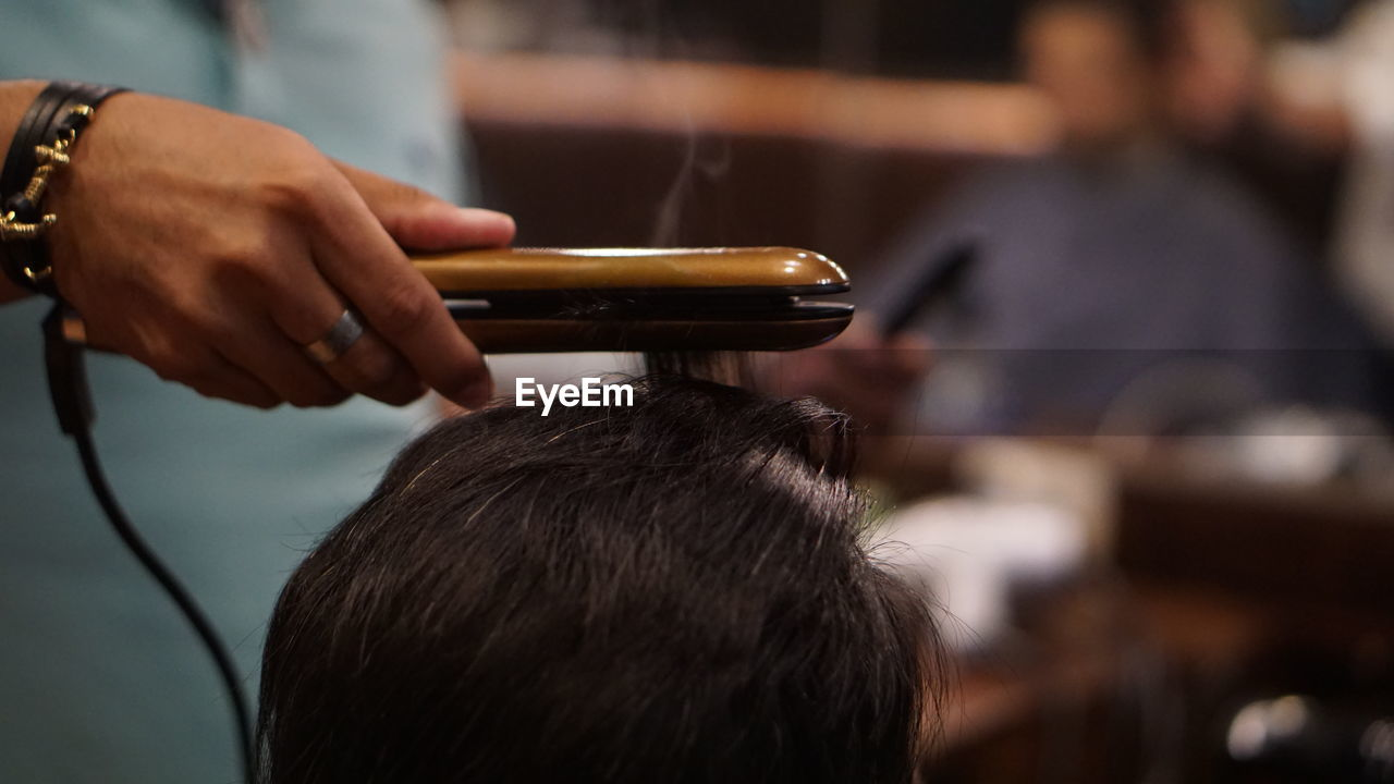 real people, human hand, hand, holding, focus on foreground, men, hairdresser, human body part, lifestyles, adult, people, hair, hair salon, indoors, human hair, hairstyle, two people, women, occupation, barber, barber shop, combing