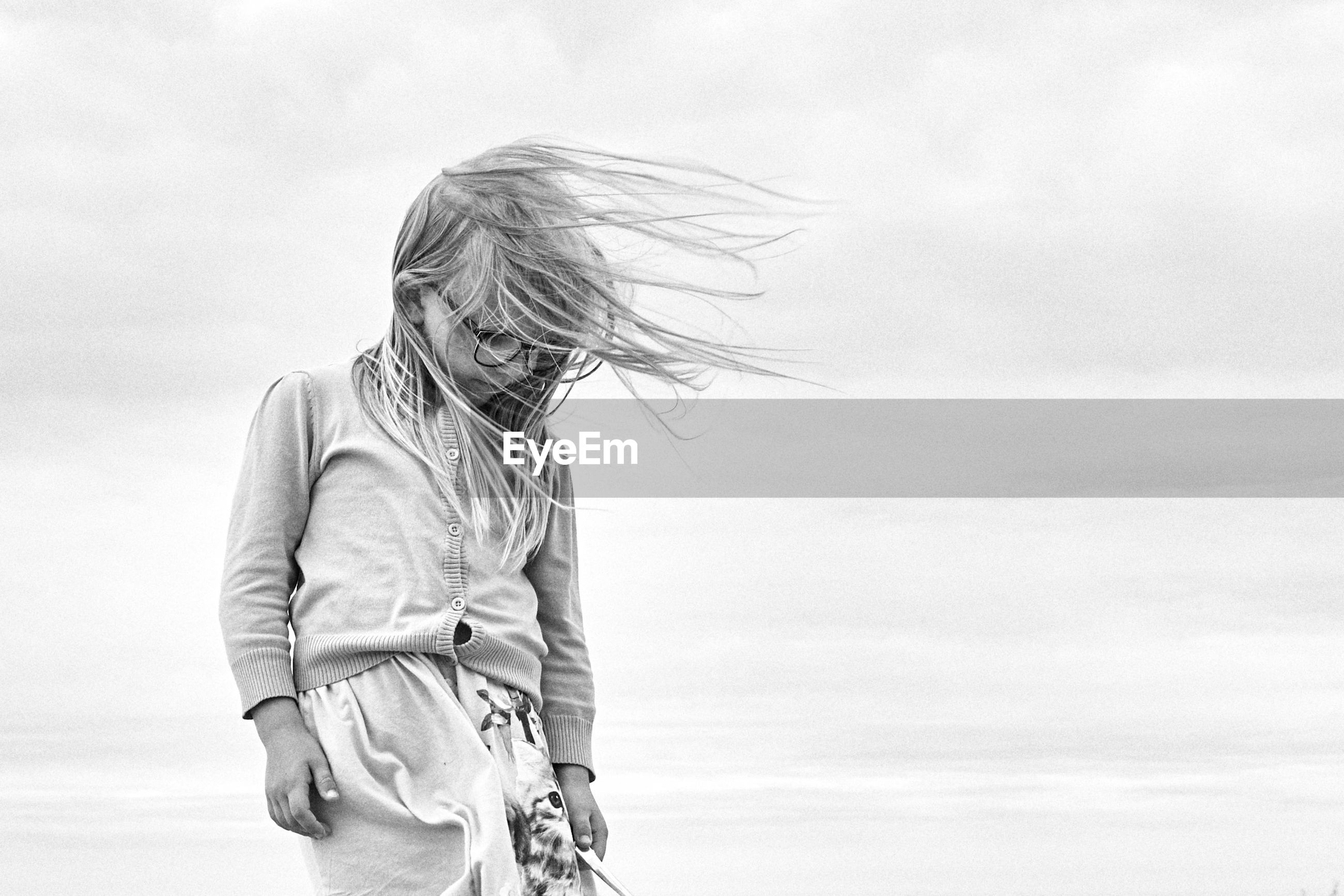 Girl with tousled hair standing against sky
