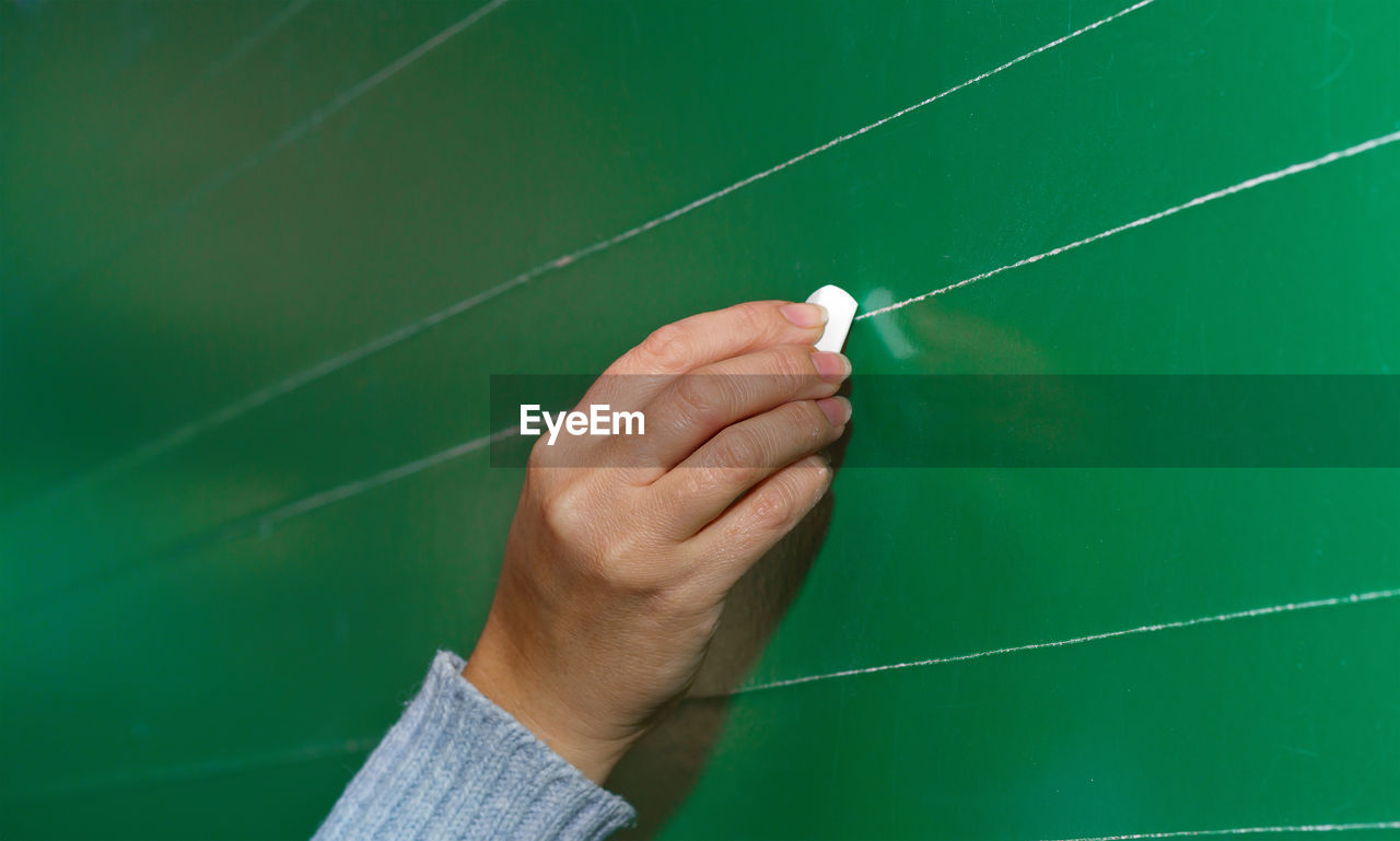 Cropped image of teacher drawing on blackboard