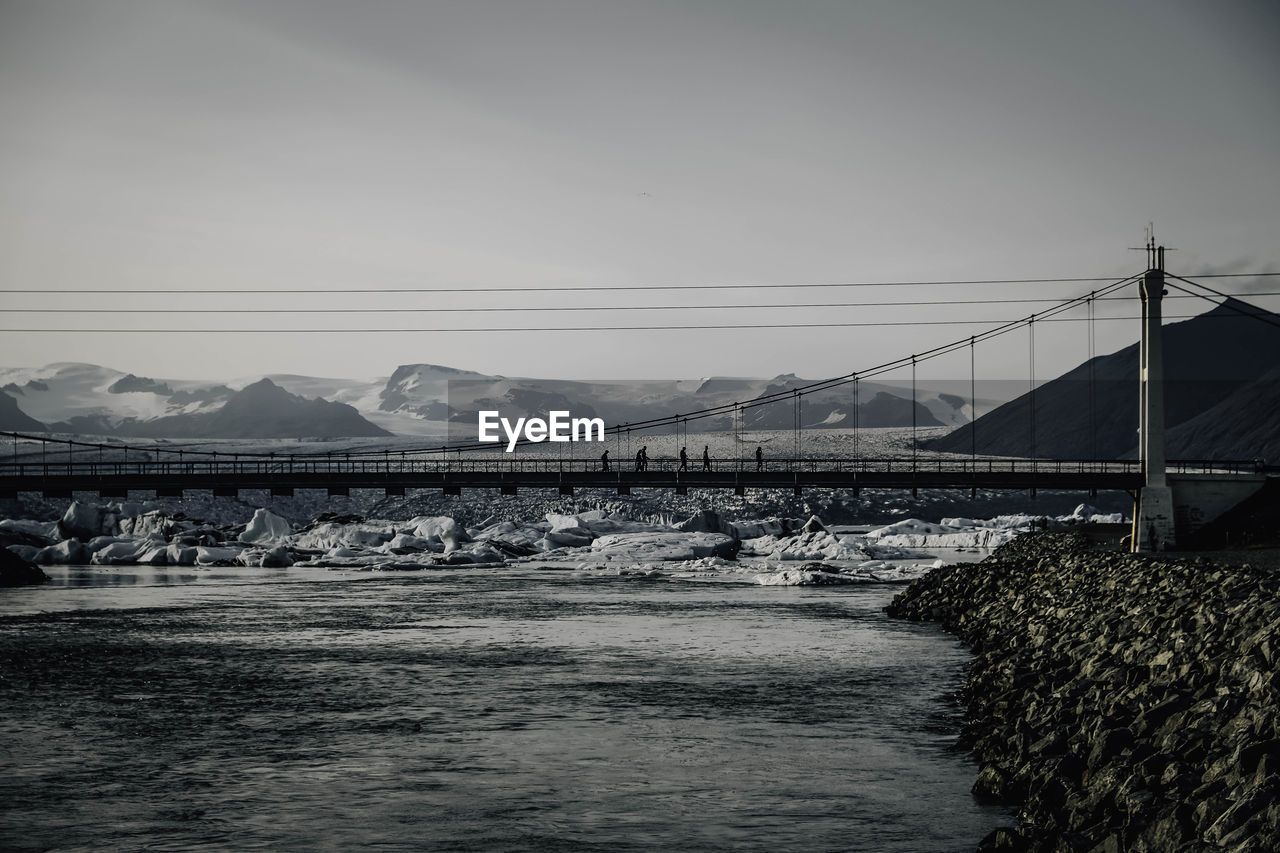 water, connection, sky, bridge, built structure, architecture, mountain, nature, bridge - man made structure, no people, transportation, waterfront, day, cable, river, building exterior, mountain range, scenics - nature, electricity, outdoors, flowing water