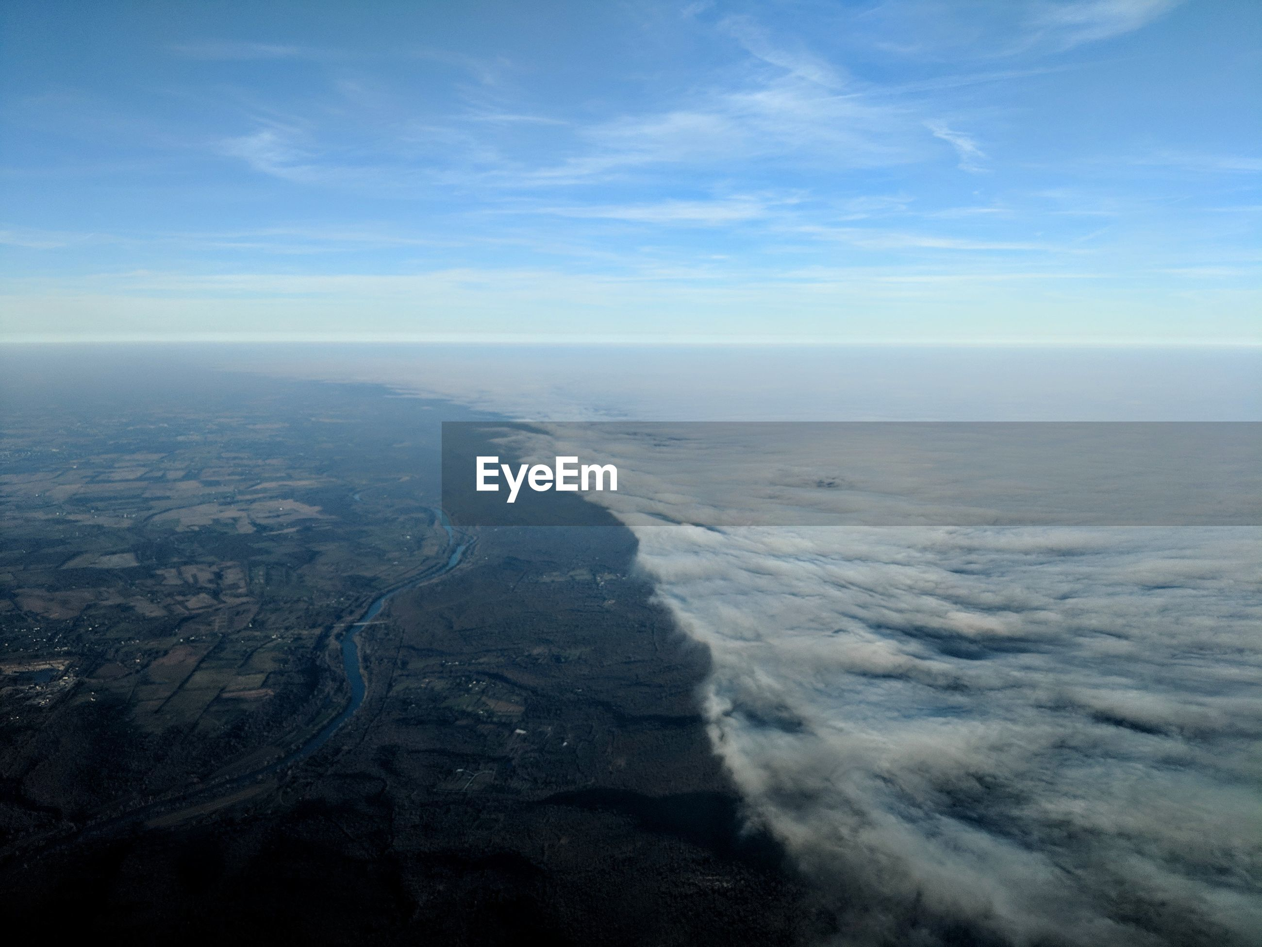Aerial view of landscape and low cloud line against sky