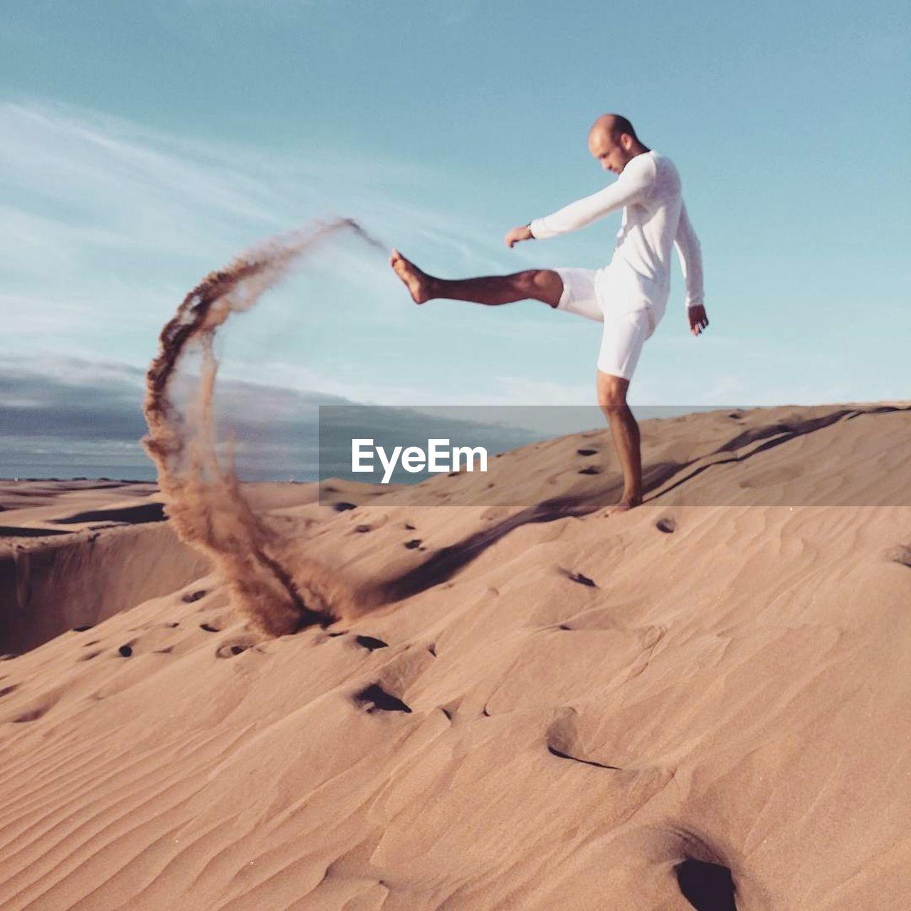 Full length of man kicking sand at maspalomas desert