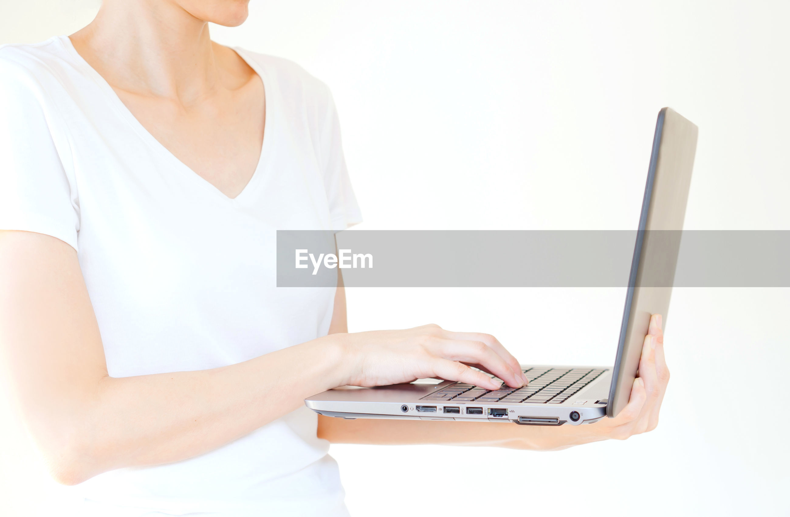 Midsection of woman using laptop against white background