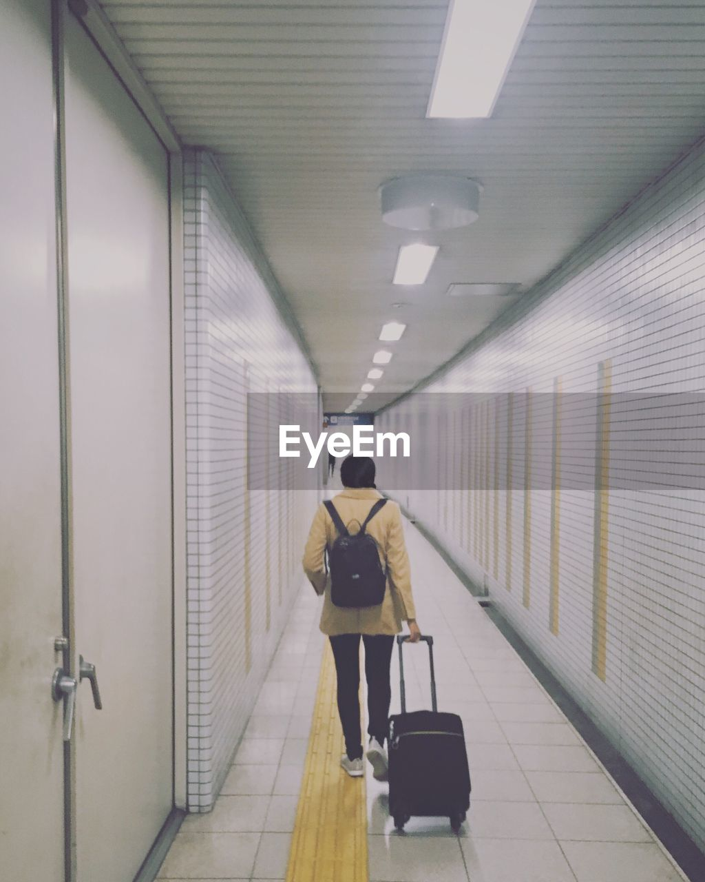 Rear view of woman walking with suitcase in corridor