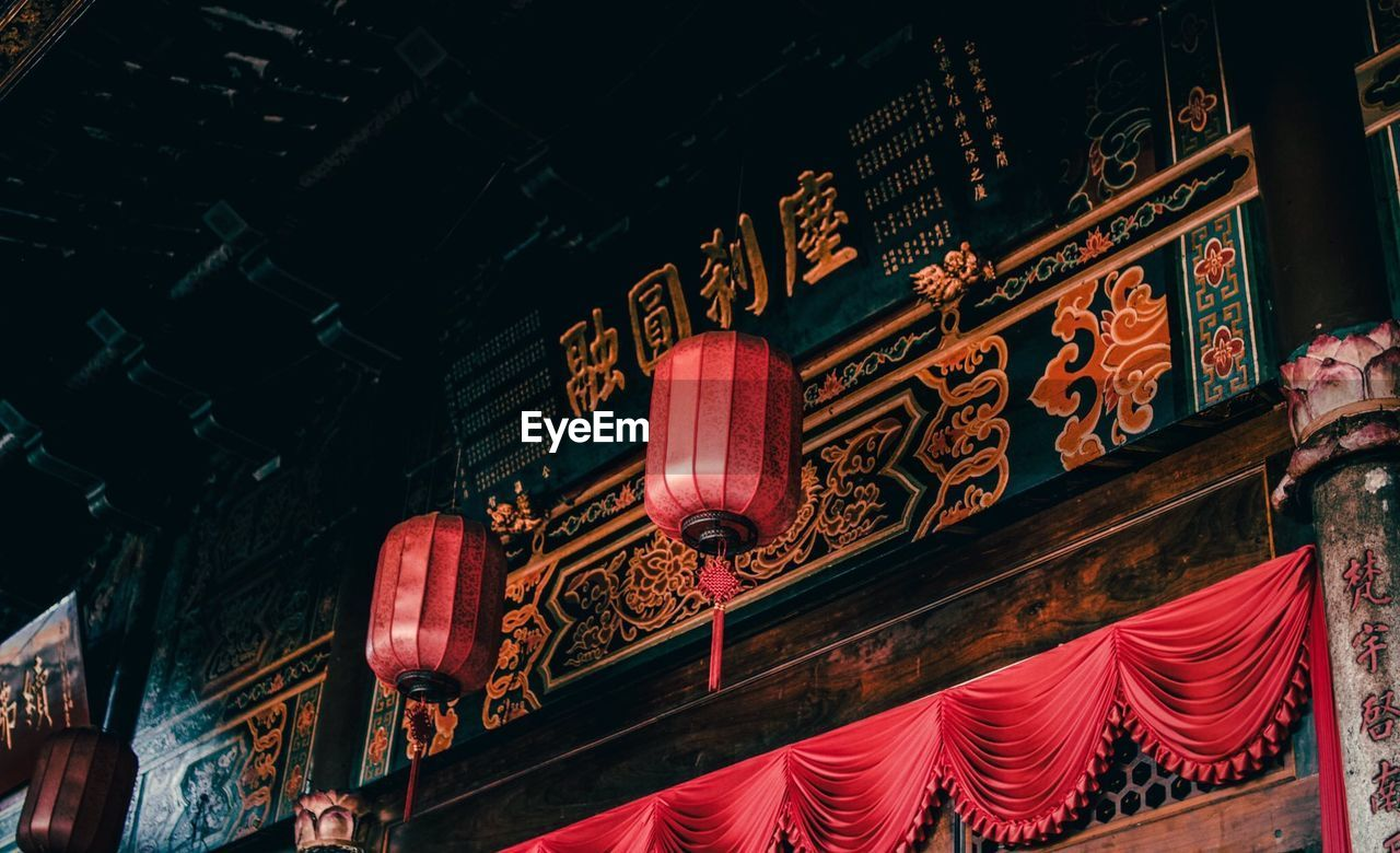 illuminated, low angle view, built structure, lighting equipment, architecture, text, script, no people, communication, non-western script, building exterior, lantern, night, building, hanging, place of worship, red, glowing, chinese lantern, electric lamp