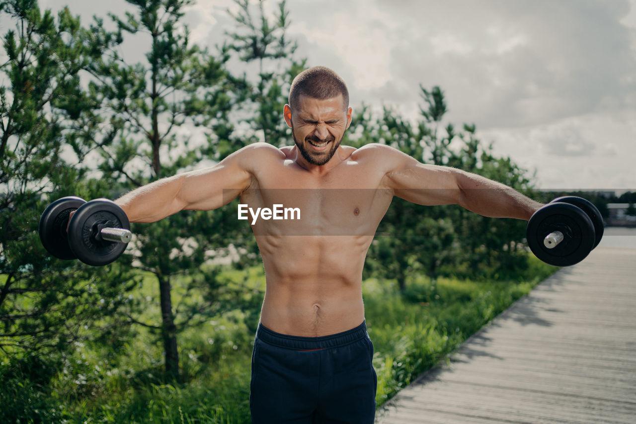 F shirtless man exercising outdoors