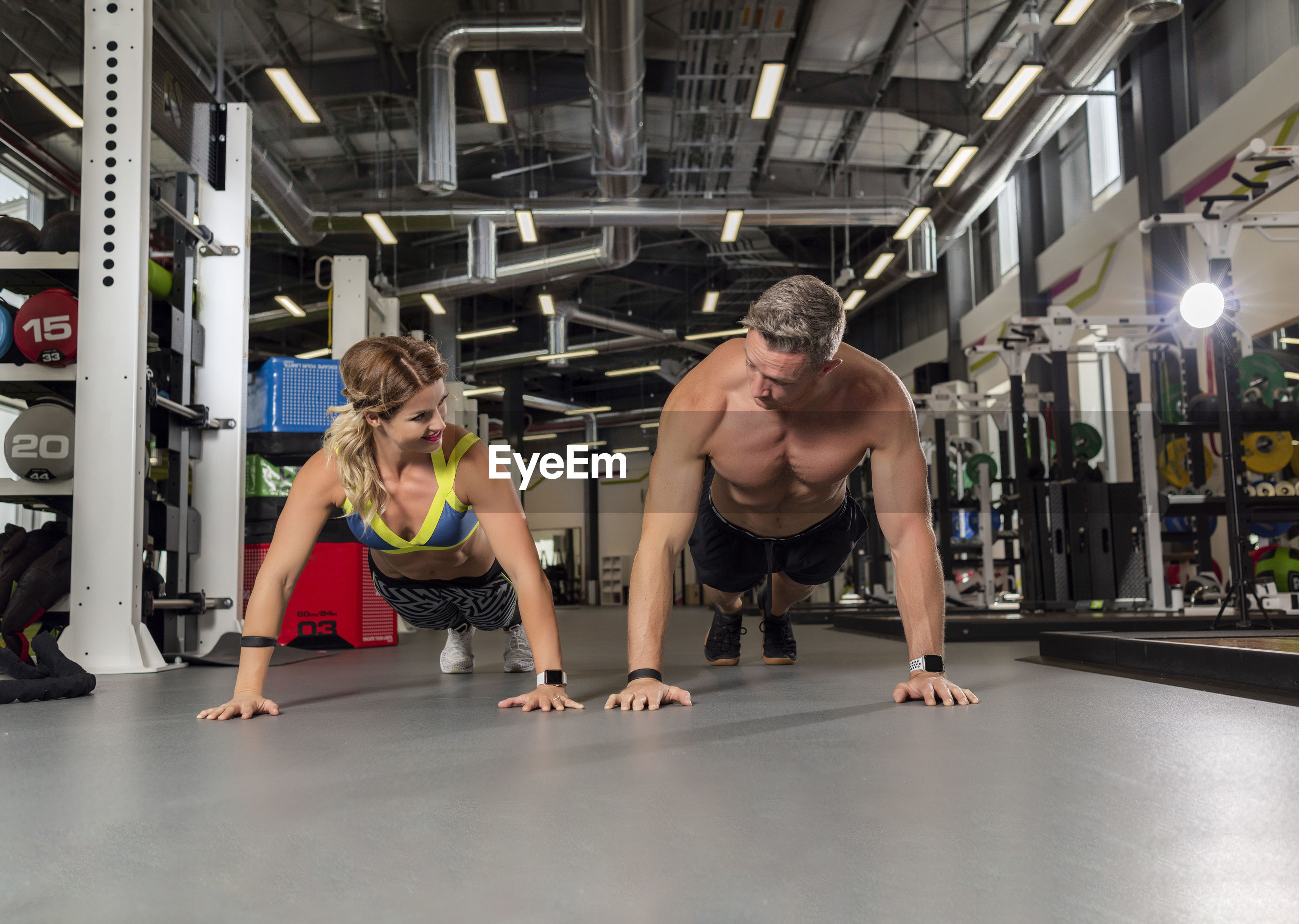 Full length of couple doing push-ups at gym