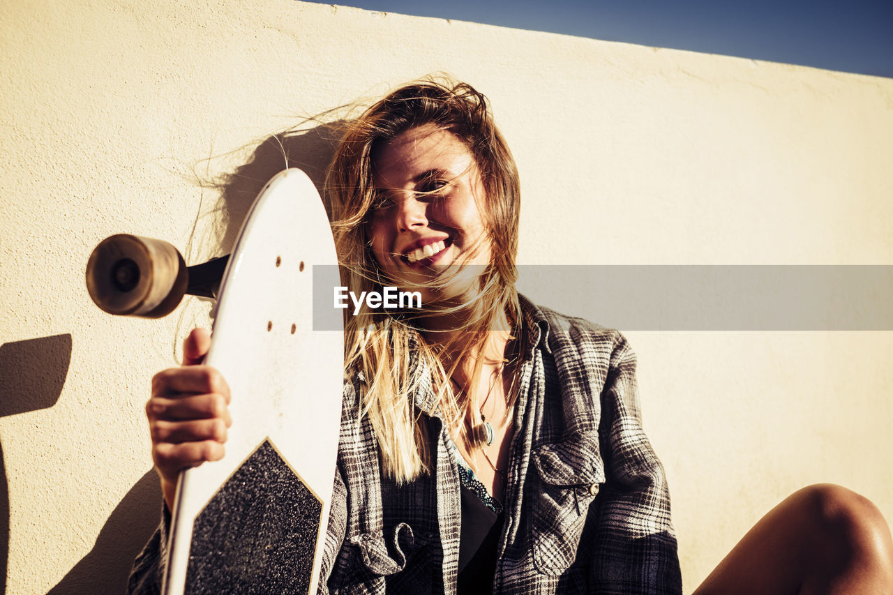 Close-Up Of Young Woman Holding Skateboard By Wall