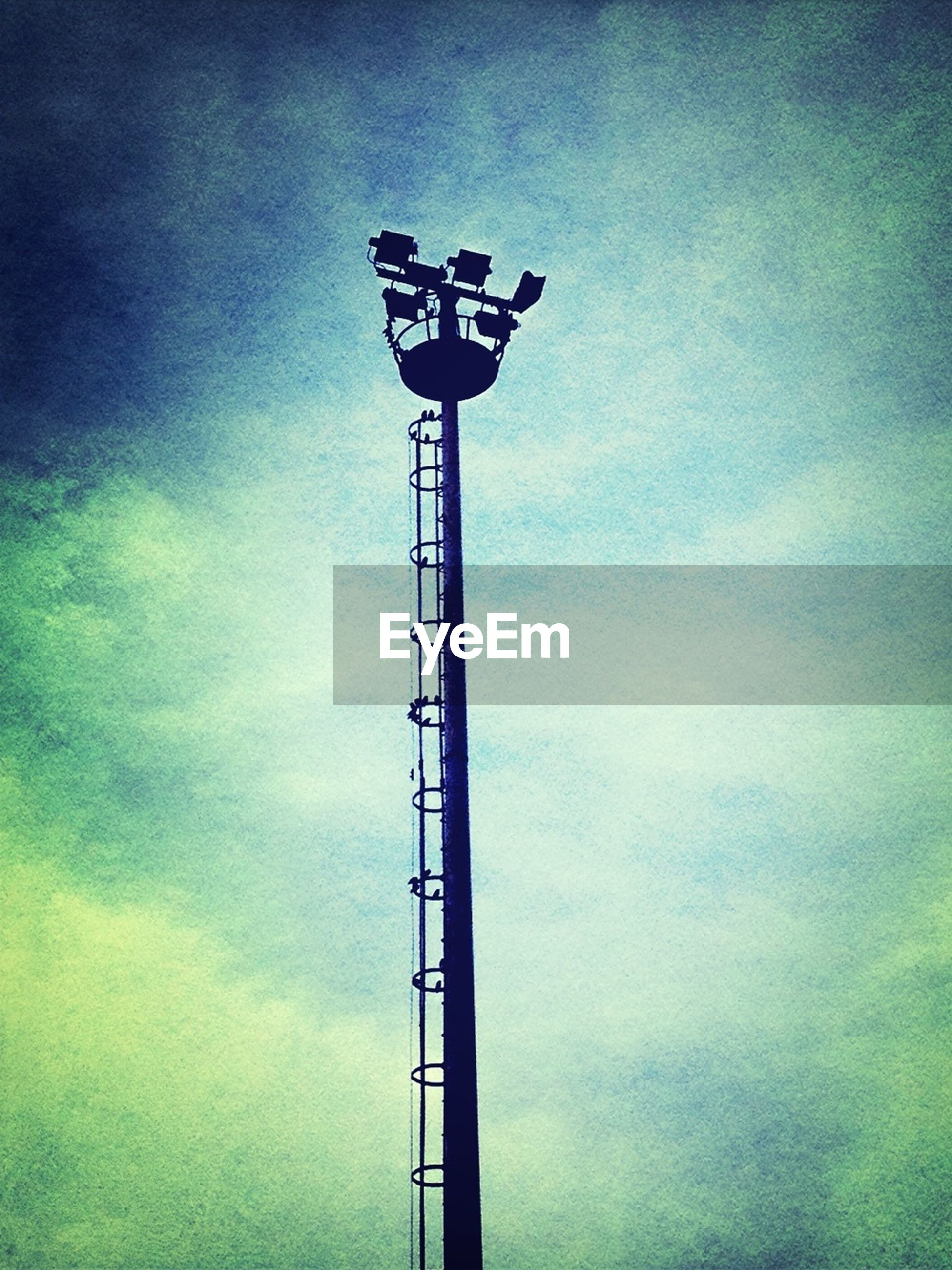 low angle view, sky, cloud - sky, tall - high, lighting equipment, cloudy, technology, street light, metal, electricity, tower, built structure, silhouette, cloud, dusk, outdoors, day, communications tower, no people, communication