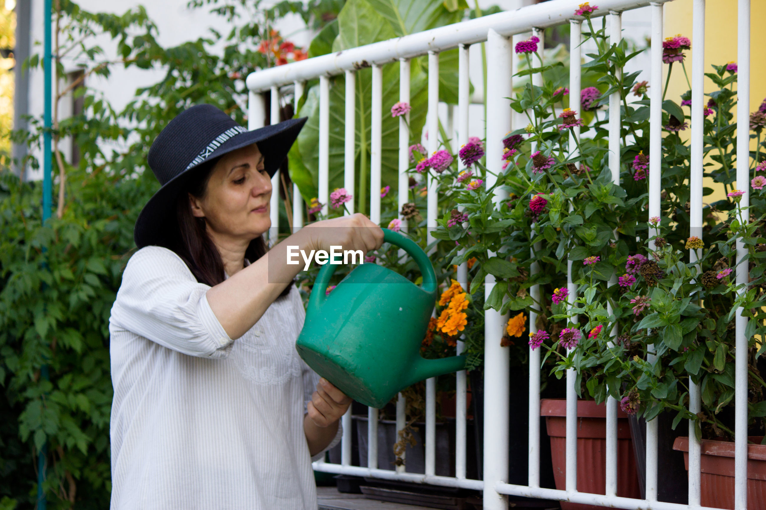 Woman watering while standing by plants