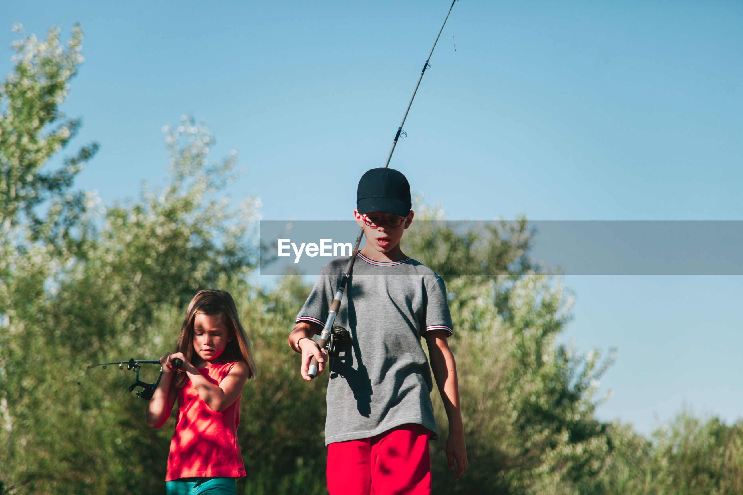 Siblings carrying fishing rods against clear blue sky