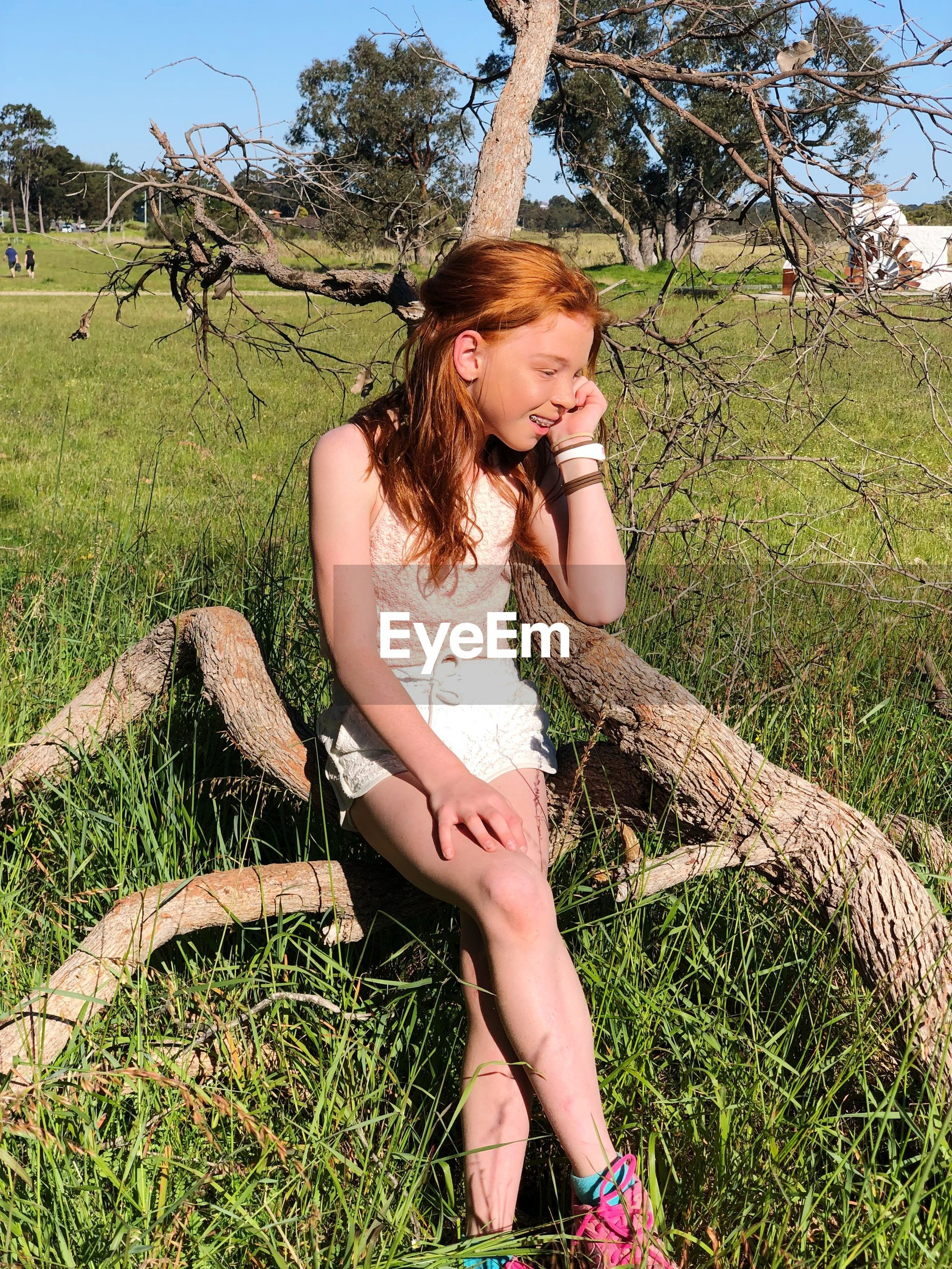 Girl sitting on grassy field during sunny day