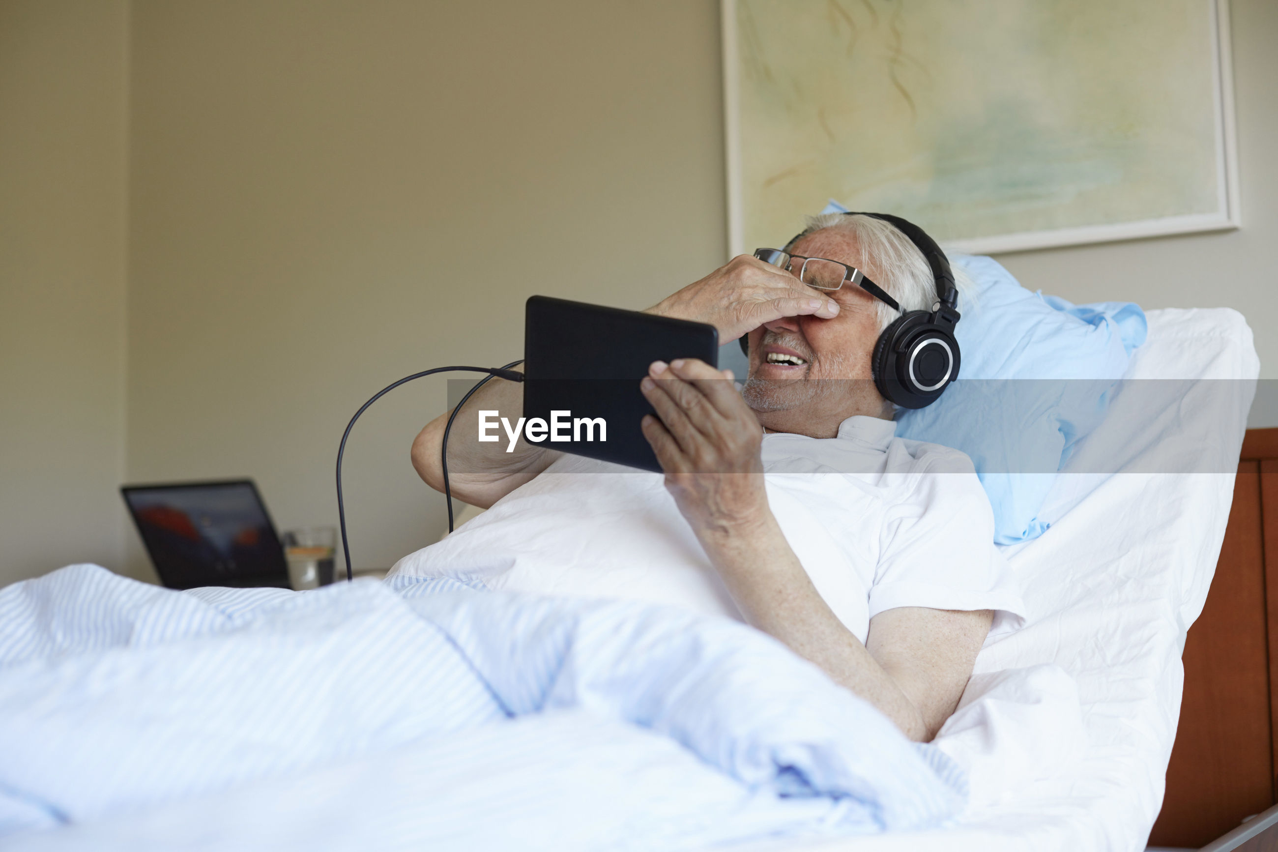 MIDSECTION OF MAN USING MOBILE PHONE WHILE SITTING ON BED IN ROOM