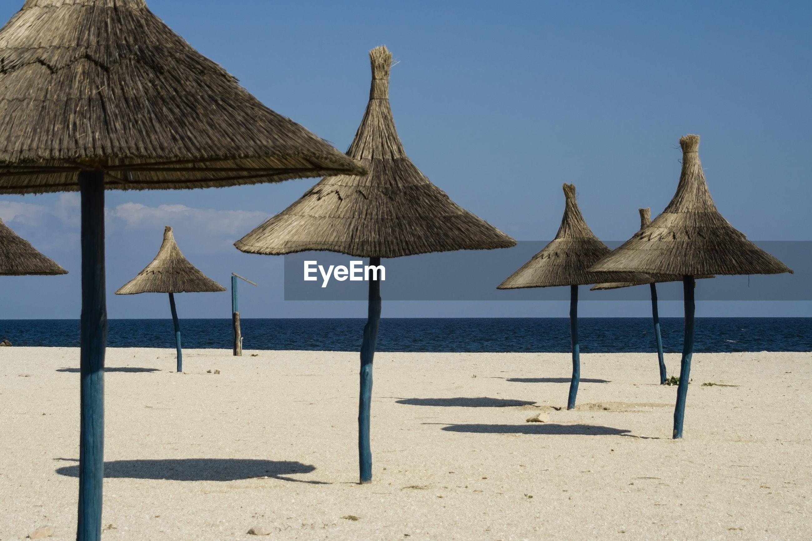 UMBRELLAS ON BEACH AGAINST CLEAR SKY