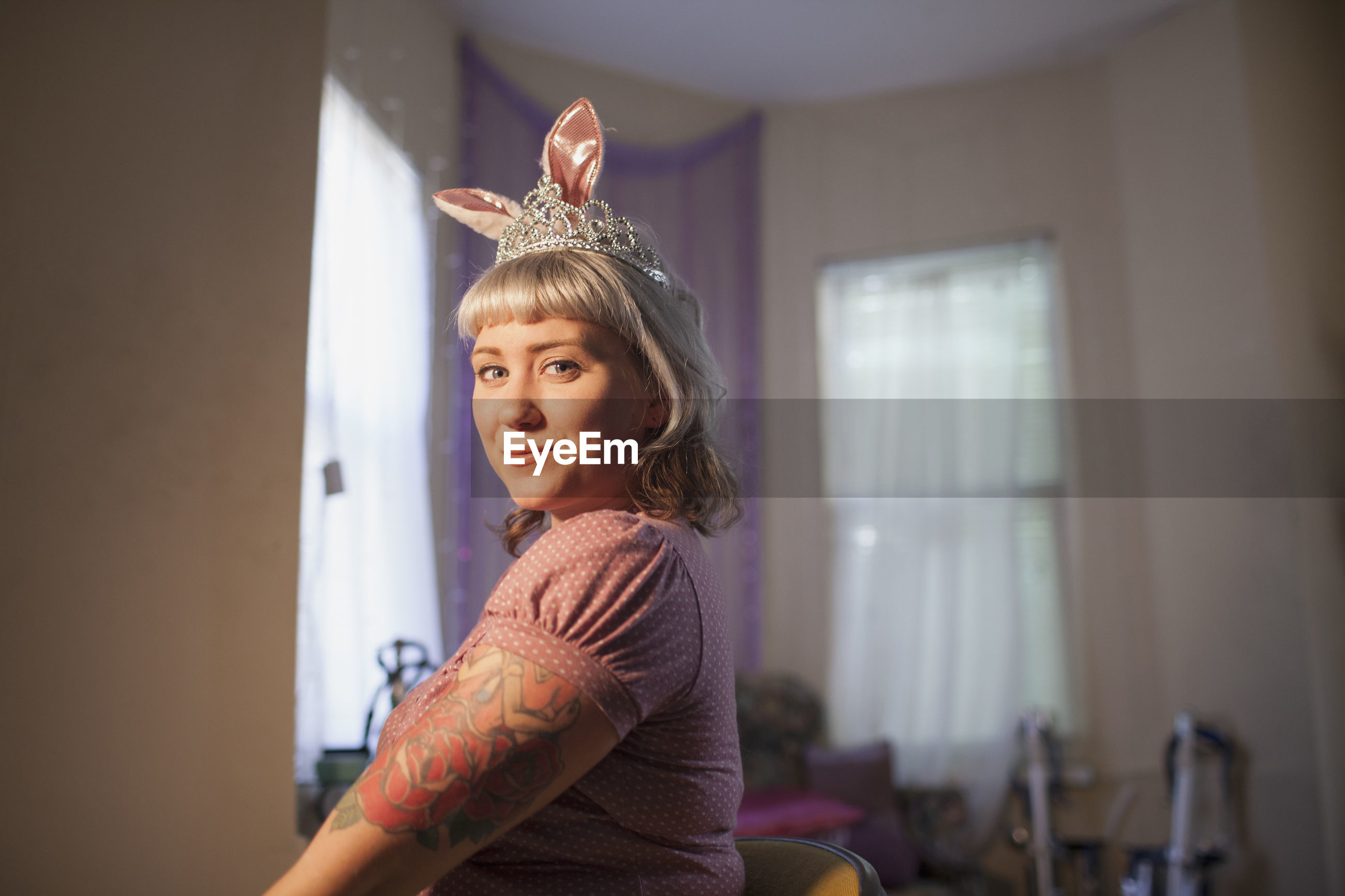 Young woman in front of mirror wearing bunny ears