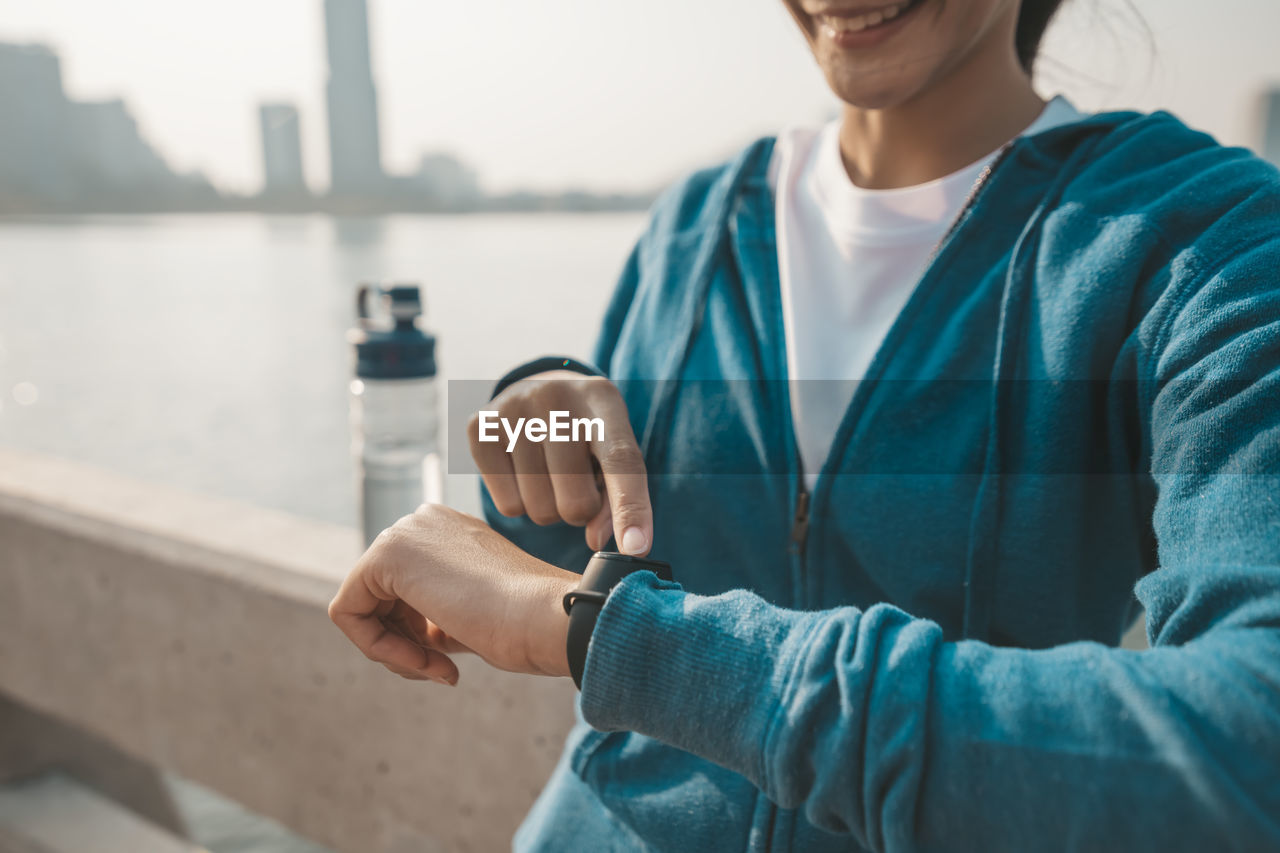 Midsection of woman touching smart watch while standing outdoors
