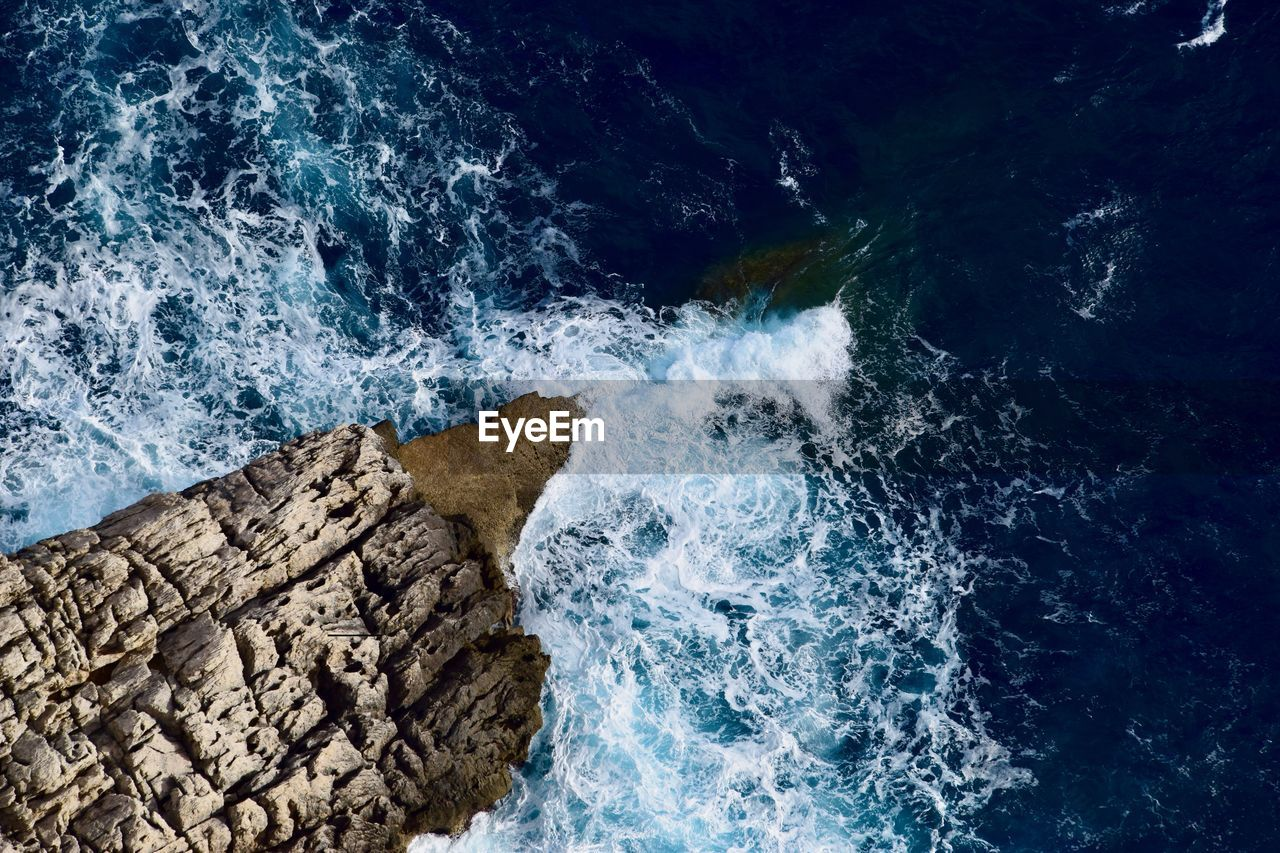 High Angle View Of Sea Waves Splashing On Rocks