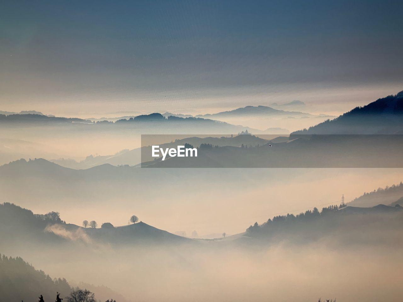 mountain, scenics - nature, beauty in nature, tranquil scene, fog, tranquility, mountain range, sky, idyllic, non-urban scene, environment, no people, nature, hazy, majestic, sunset, landscape, remote, outdoors, mountain peak