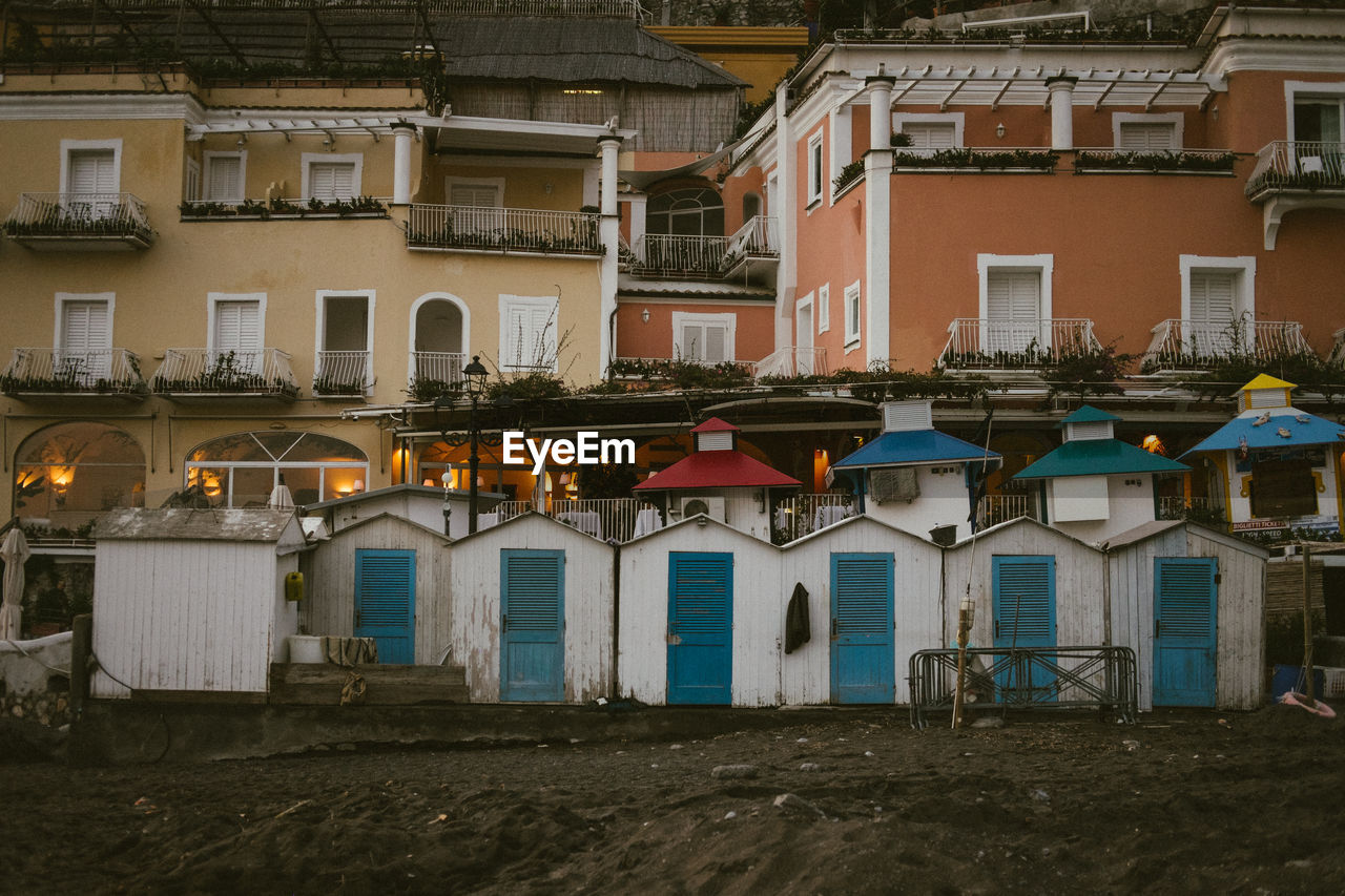 built structure, building exterior, architecture, building, residential district, window, city, no people, day, outdoors, nature, land, house, side by side, beach, in a row, roof, town, multi colored, sand, location, apartment