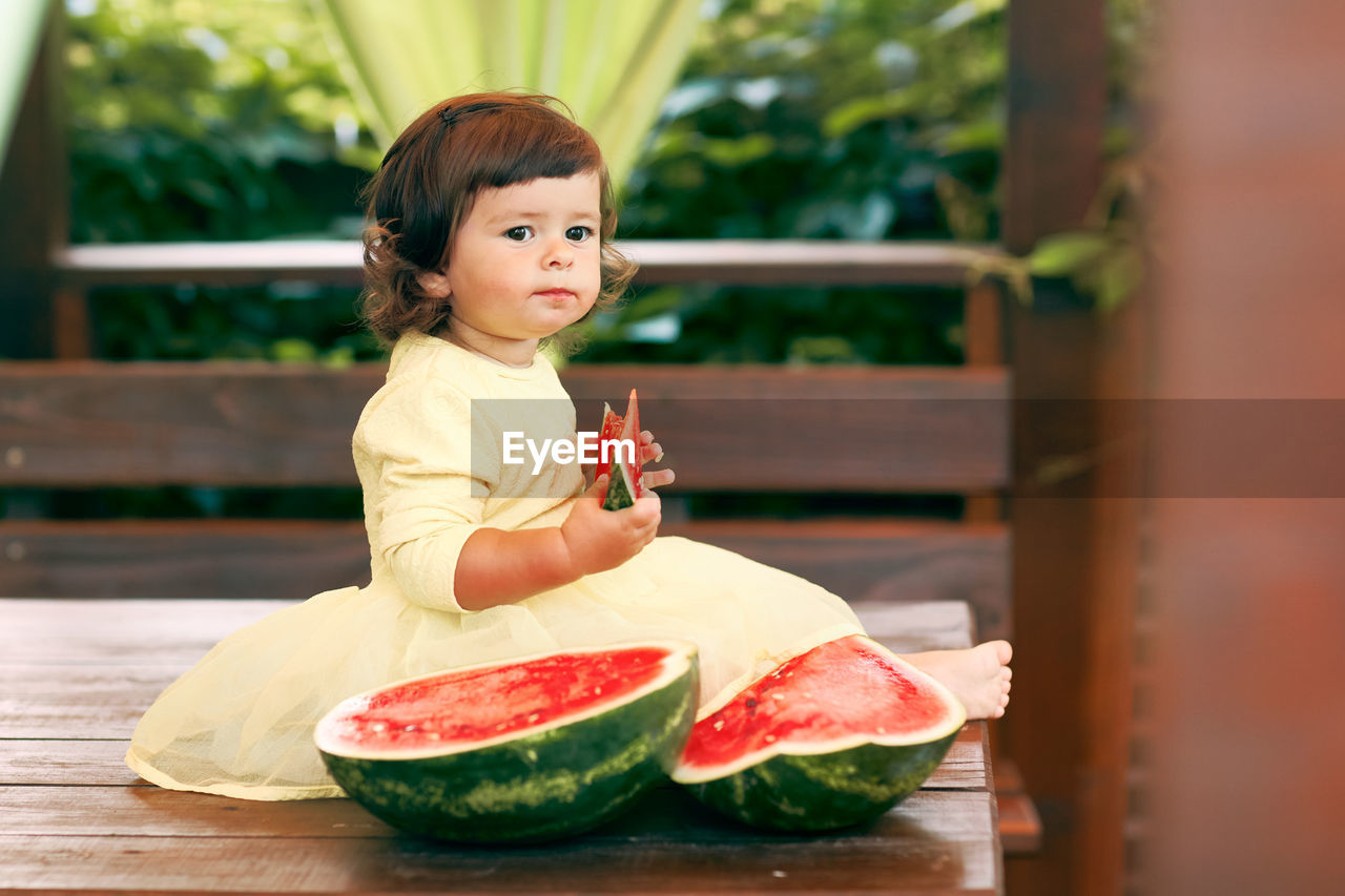 Girl eating watermelon on table