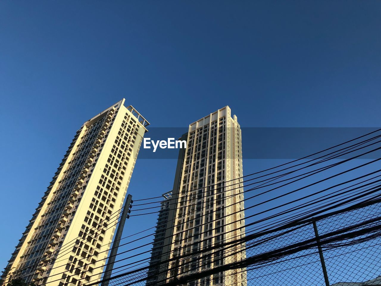 sky, built structure, architecture, building exterior, low angle view, city, clear sky, blue, office building exterior, building, tall - high, modern, copy space, skyscraper, nature, no people, office, tower, day, outdoors, financial district, power supply