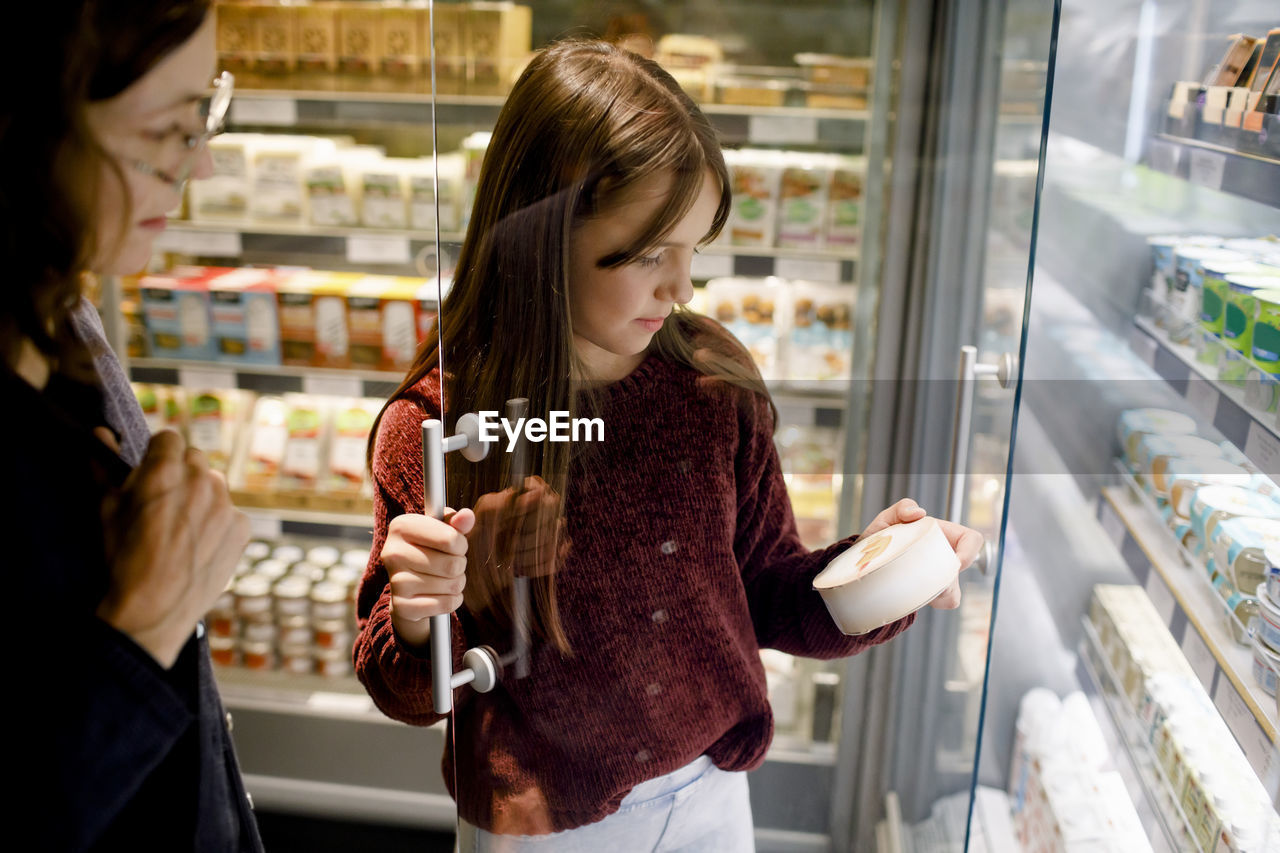 YOUNG WOMAN STANDING BY STORE AT RESTAURANT