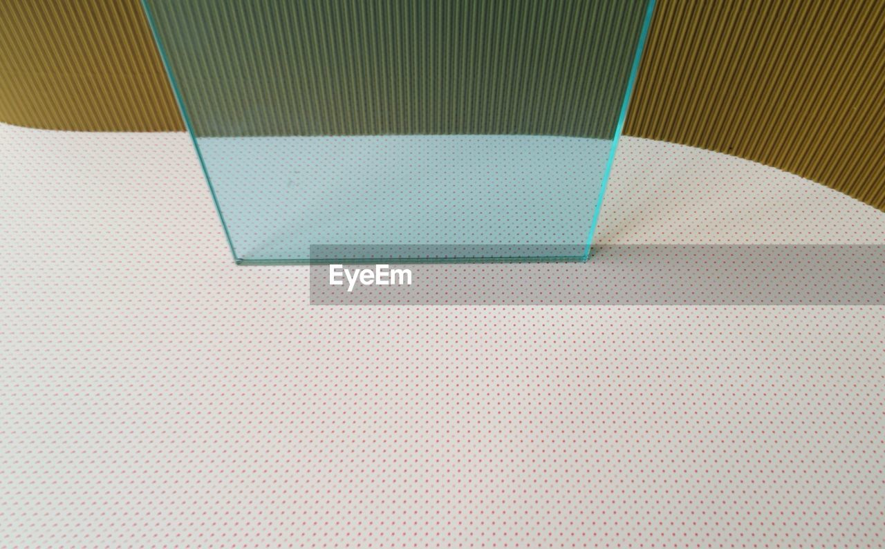 High Angle View Of Glass On White Patterned Floor