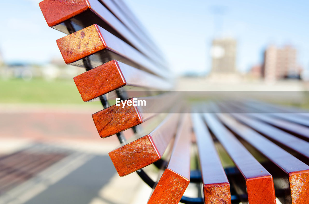 focus on foreground, built structure, building exterior, day, architecture, no people, close-up, nature, sky, outdoors, sunlight, metal, still life, selective focus, hanging, city, building, low angle view, hope - concept, large group of objects
