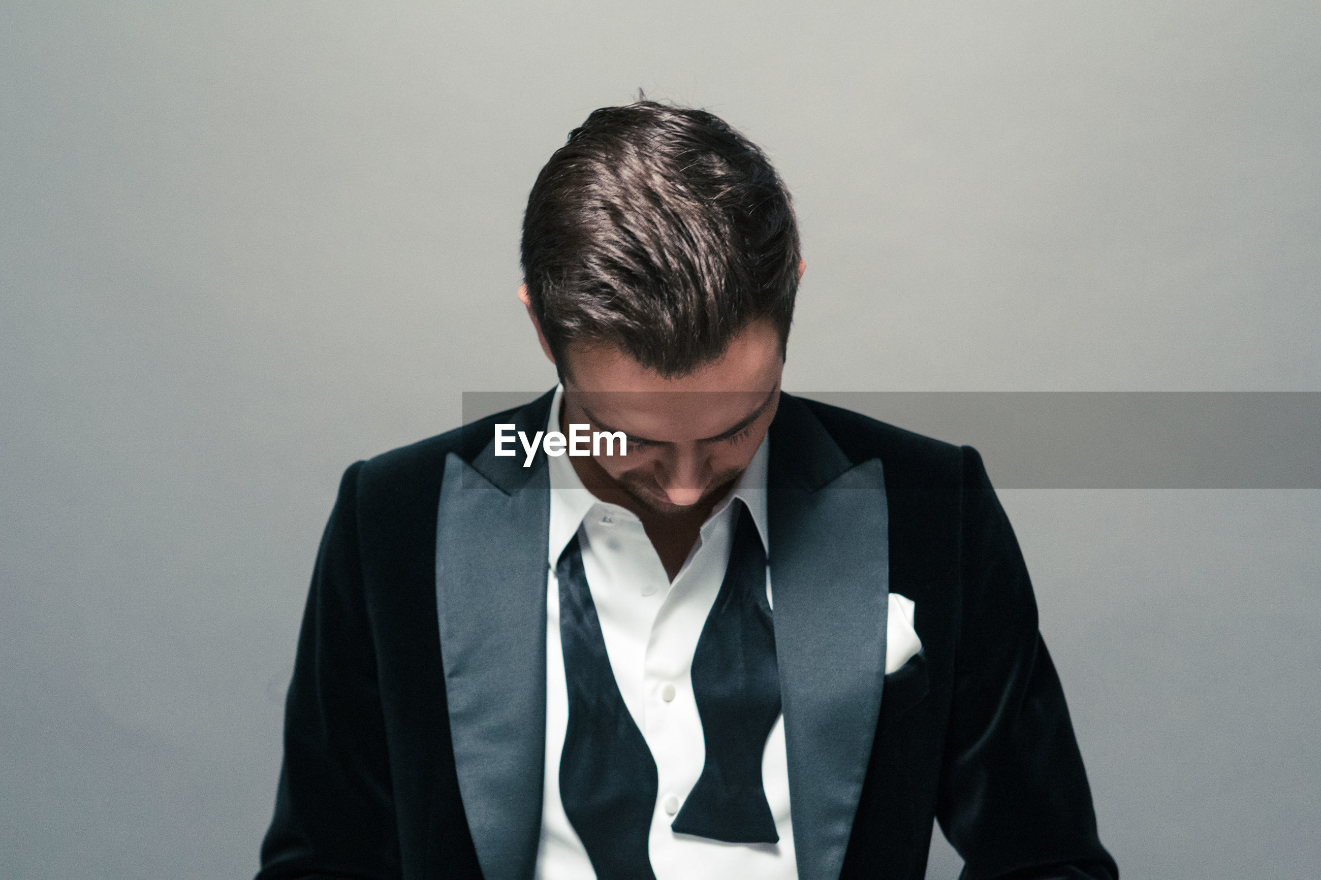 Sad young man in suit against gray background