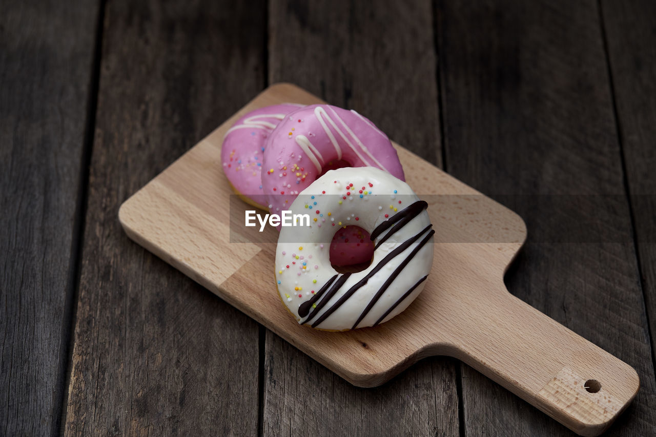 Close-up of donuts on cutting board over table