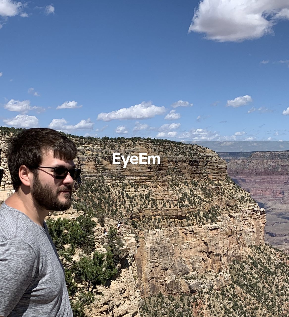 SIDE VIEW OF YOUNG MAN AGAINST SUNGLASSES ON MOUNTAIN