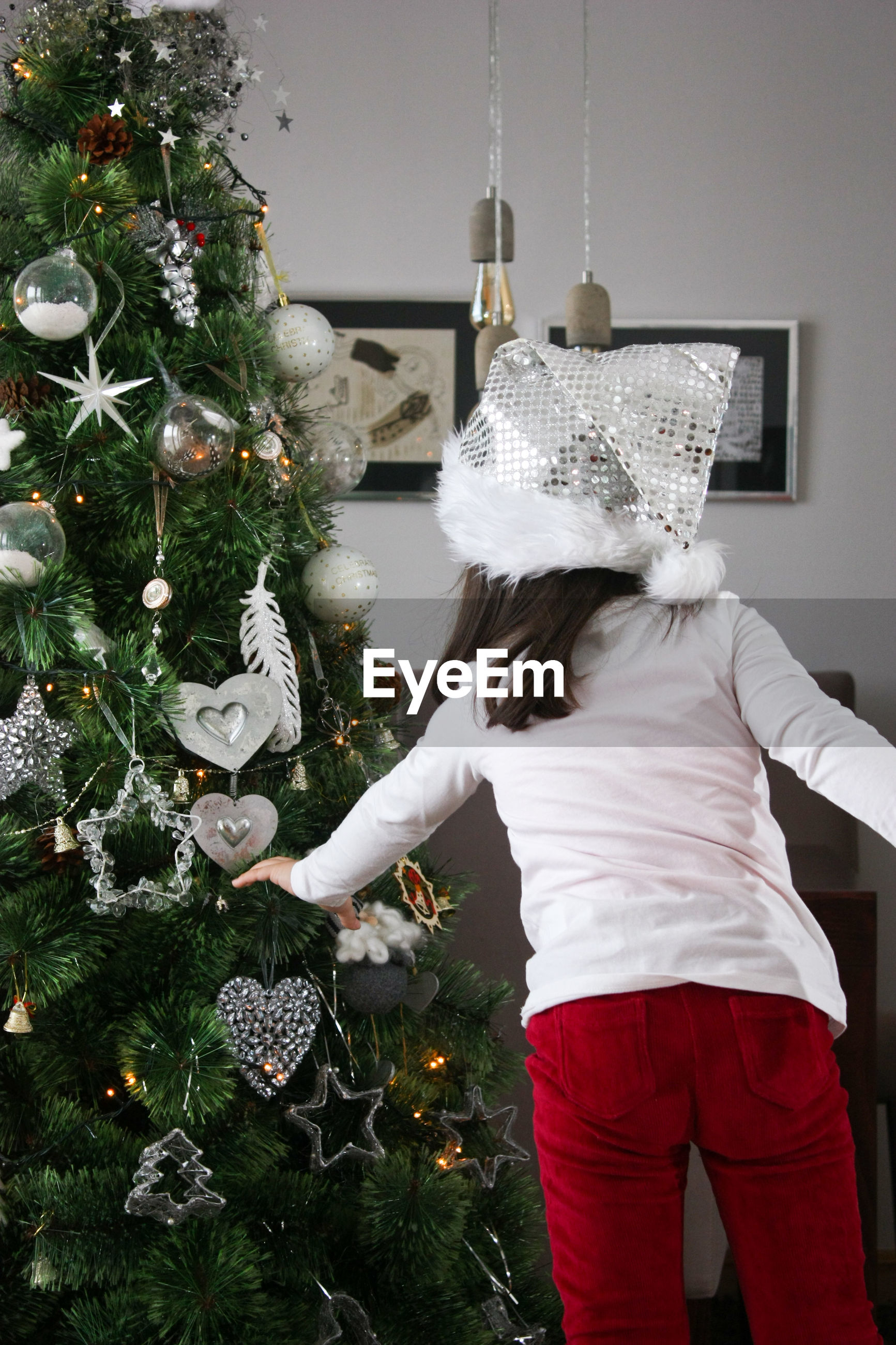 Rear view of girl decorating christmas tree at home