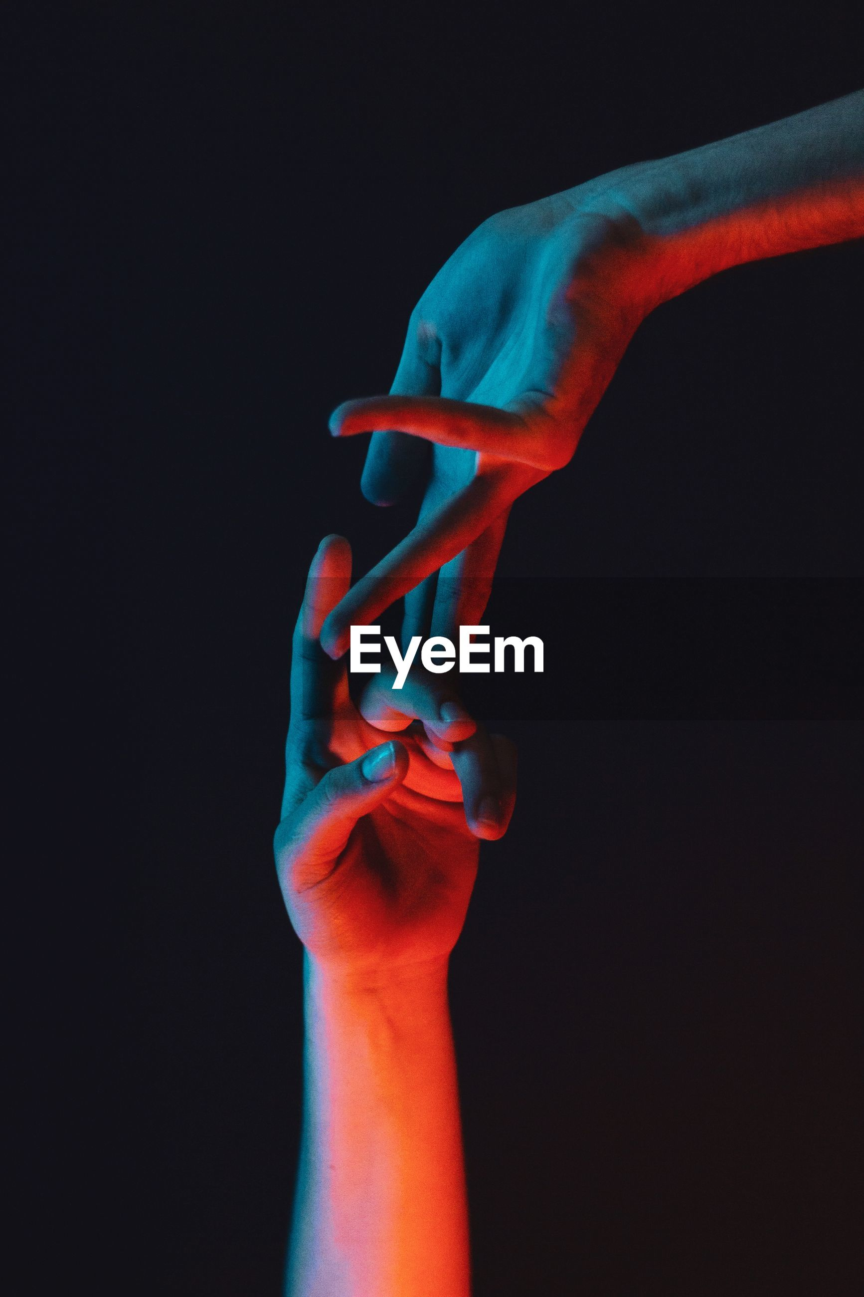 Cropped image of people touching fingers against black background