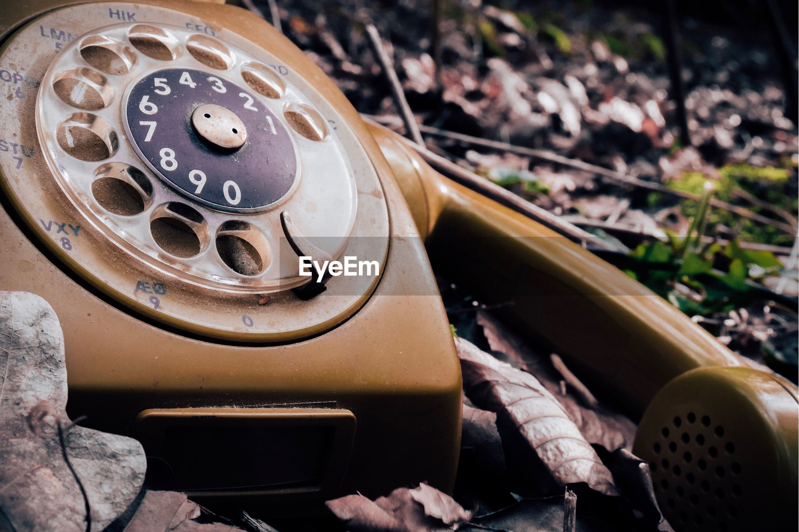 Close-up of old rotary phone on land