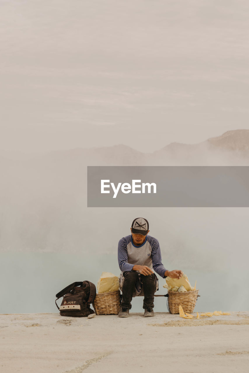 real people, front view, one person, lifestyles, mountain, full length, nature, men, sitting, day, young men, young adult, leisure activity, fog, mid adult, sky, casual clothing, one animal, outdoors