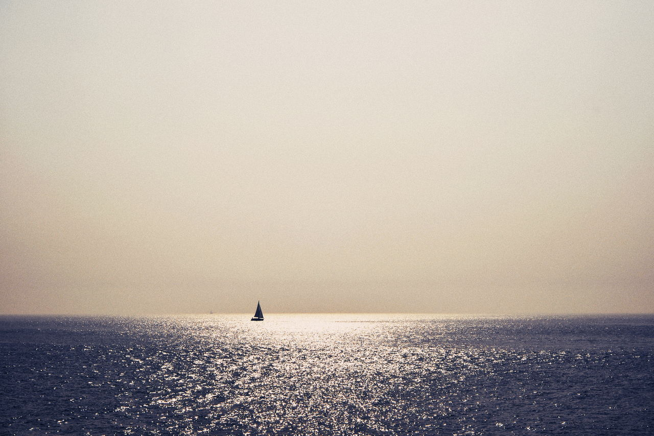 sea, water, sky, horizon over water, horizon, scenics - nature, copy space, beauty in nature, tranquil scene, tranquility, nautical vessel, nature, waterfront, clear sky, transportation, day, mode of transportation, no people, sailboat, outdoors