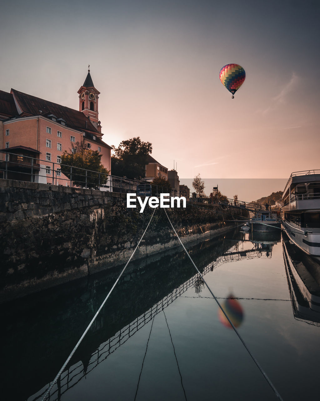 built structure, building exterior, water, architecture, transportation, sky, nature, mode of transportation, sunset, reflection, hot air balloon, nautical vessel, waterfront, adventure, building, balloon, mid-air, river, flying, outdoors