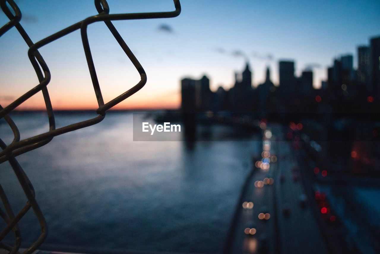 sky, architecture, built structure, water, transportation, sunset, no people, city, nature, building exterior, connection, railing, dusk, mode of transportation, outdoors, bridge, travel, focus on foreground, travel destinations, bridge - man made structure, cityscape, skyscraper, office building exterior