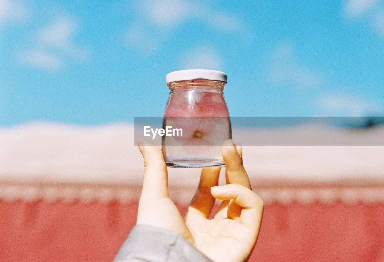 Cropped Image Of Person Holding Jar Against Sky
