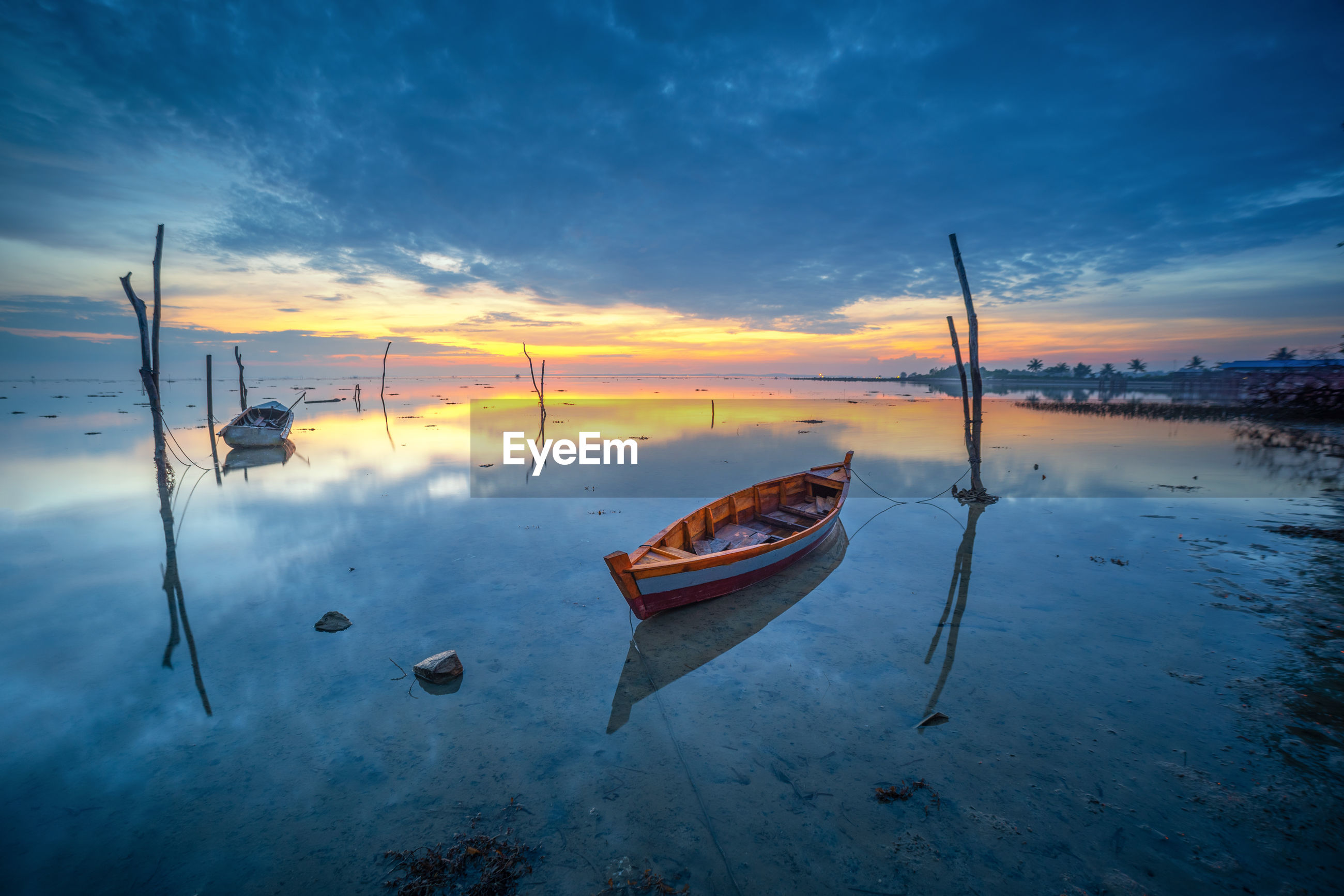 BOATS MOORED ON SEA AGAINST SKY AT SUNSET