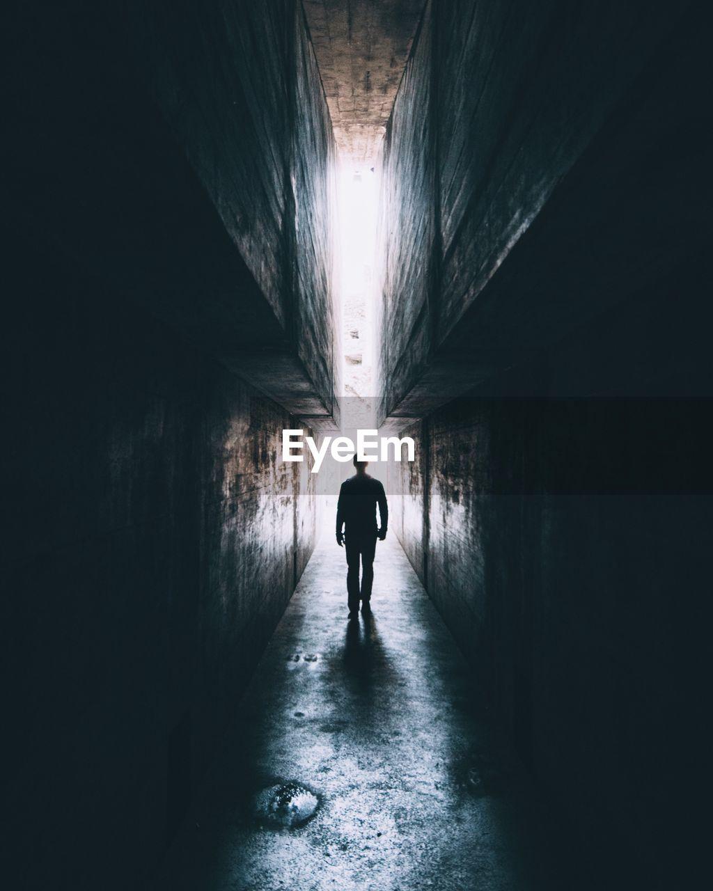 Rear View Of Silhouette Man Walking In Tunnel