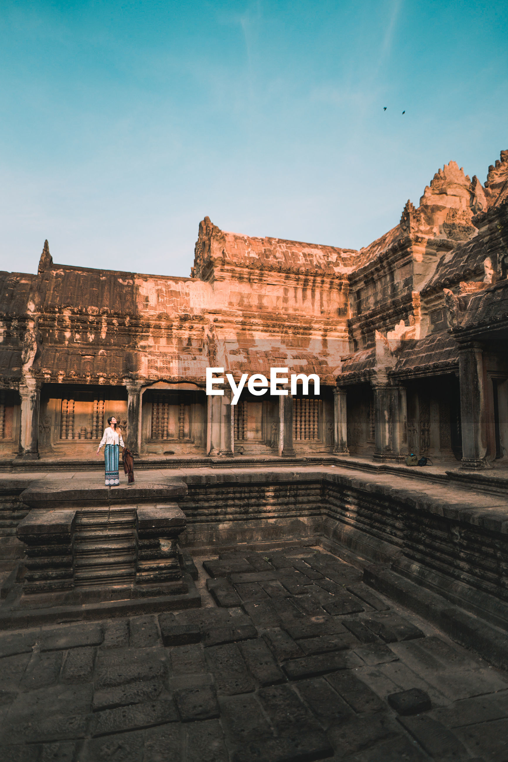 Full length of woman standing at ancient temple against sky