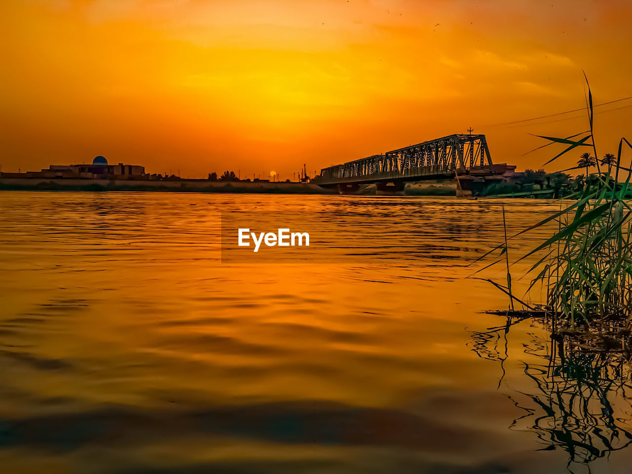 sunset, sky, orange color, water, built structure, architecture, reflection, nature, bridge - man made structure, waterfront, beauty in nature, river, no people, cloud - sky, outdoors, transportation, silhouette, scenics, building exterior, tree