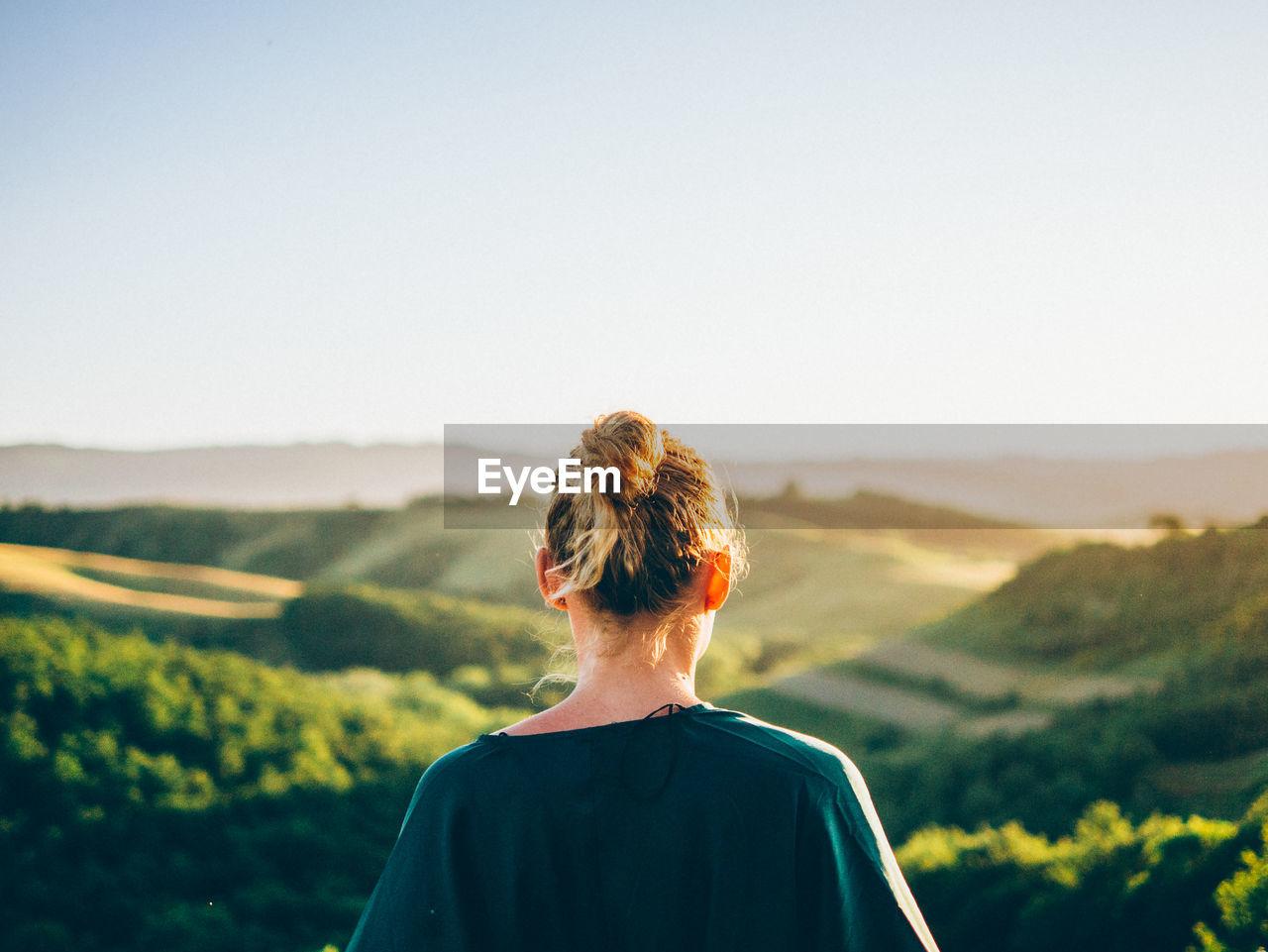 Rear View Of Blond Woman Against Landscape