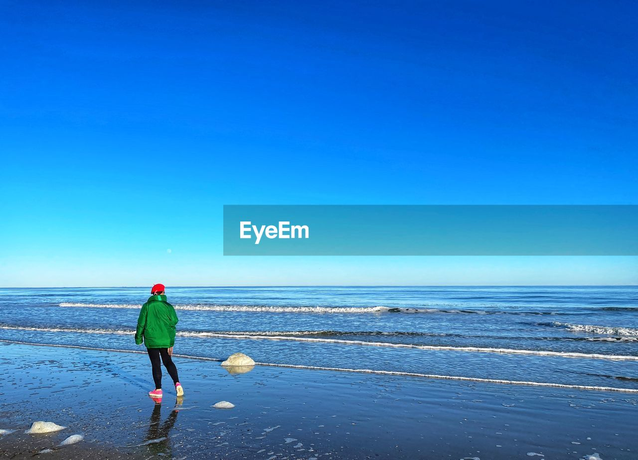 REAR VIEW OF PERSON ON BEACH AGAINST CLEAR SKY