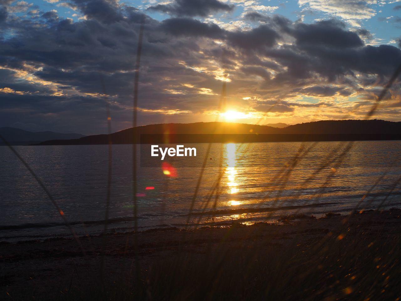 VIEW OF CALM LAKE AT SUNSET