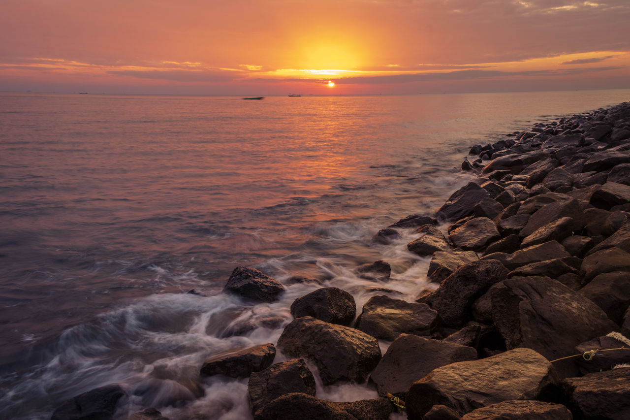 SCENIC VIEW OF ROCKY BEACH DURING SUNSET