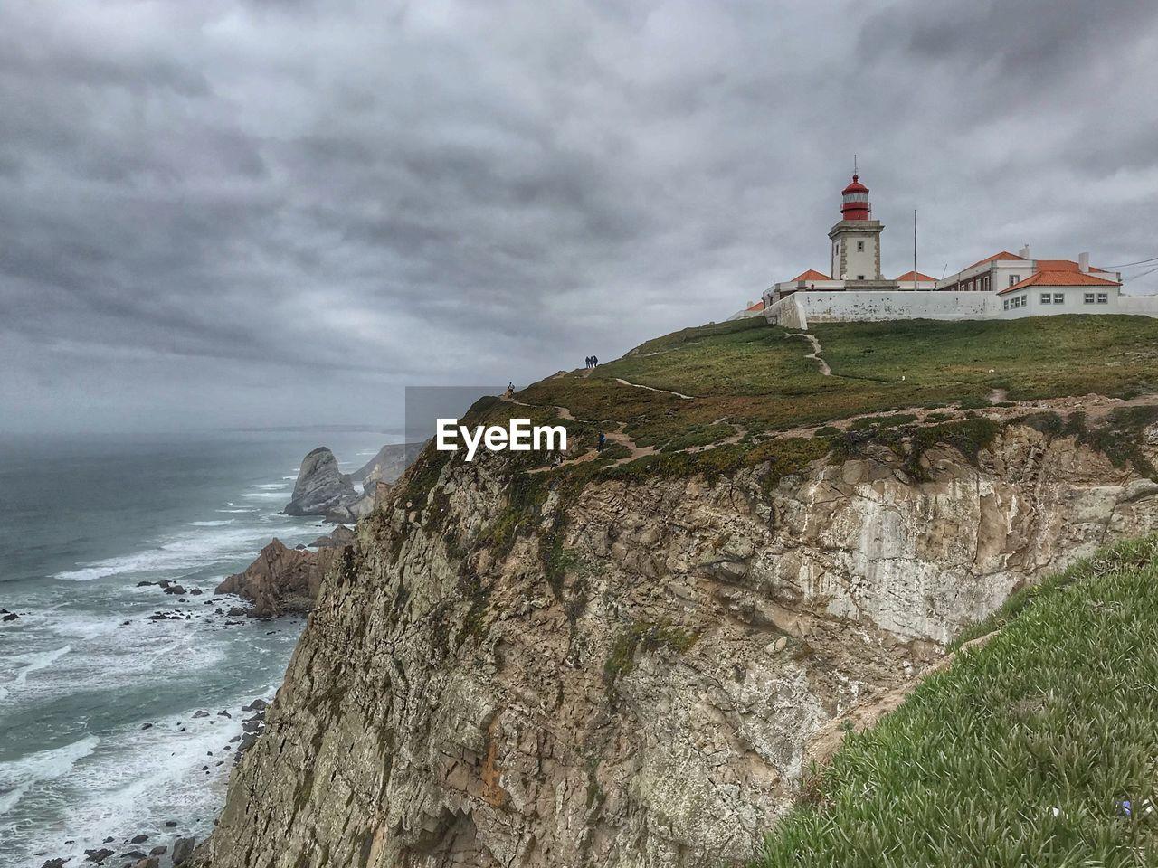 Lighthouse On Mountain By Sea Against Cloudy Sky